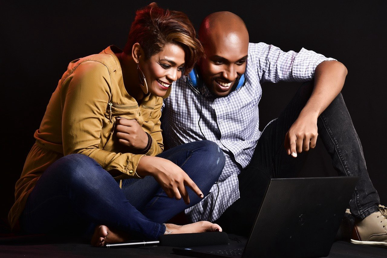 Two people smile while looking at a laptop screen.