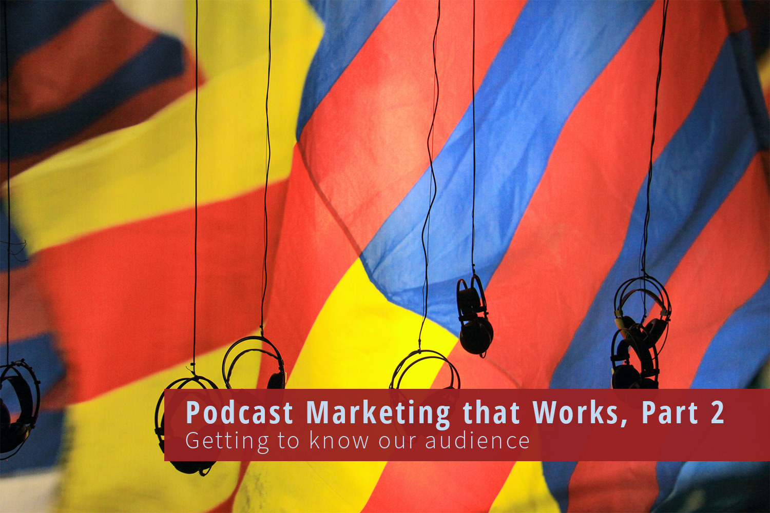 A bright hot air balloon of yellows, reds and blues behind over the ear headphones that hang from above.