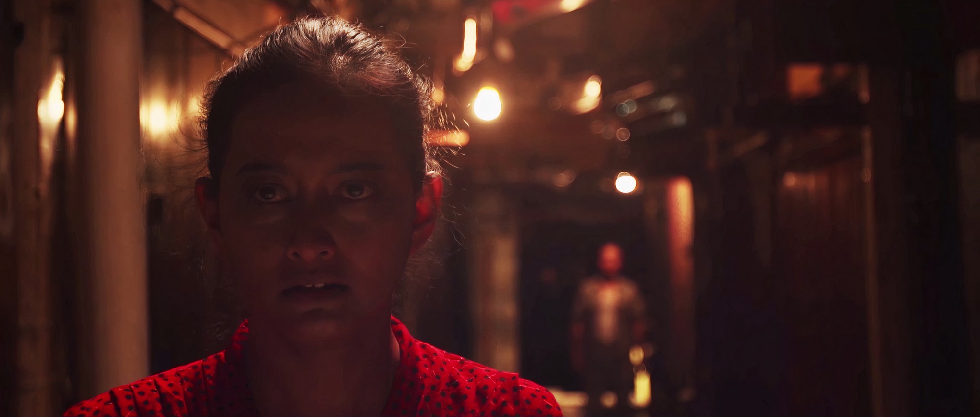 Film still from RONG of protagonist played by Maryam Supraba, wearing a red dress, walking toward the camera through a dark alleyway, followed by a man at a distance, just out of focus.