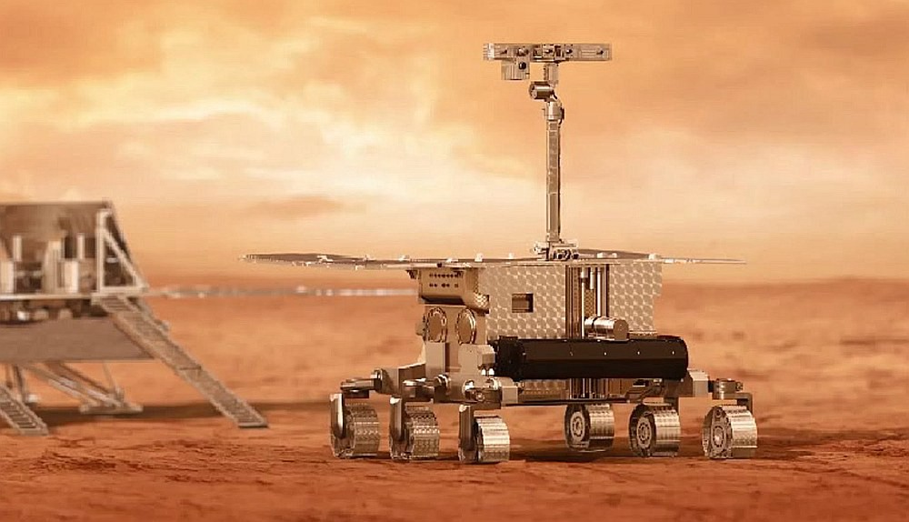 A six-wheeled craft, with a camera on top, rolls off a lander onto Mars.