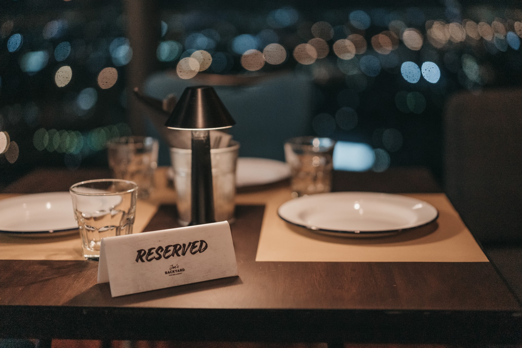 Fine dining table setting with a reserved sign sitting on it.