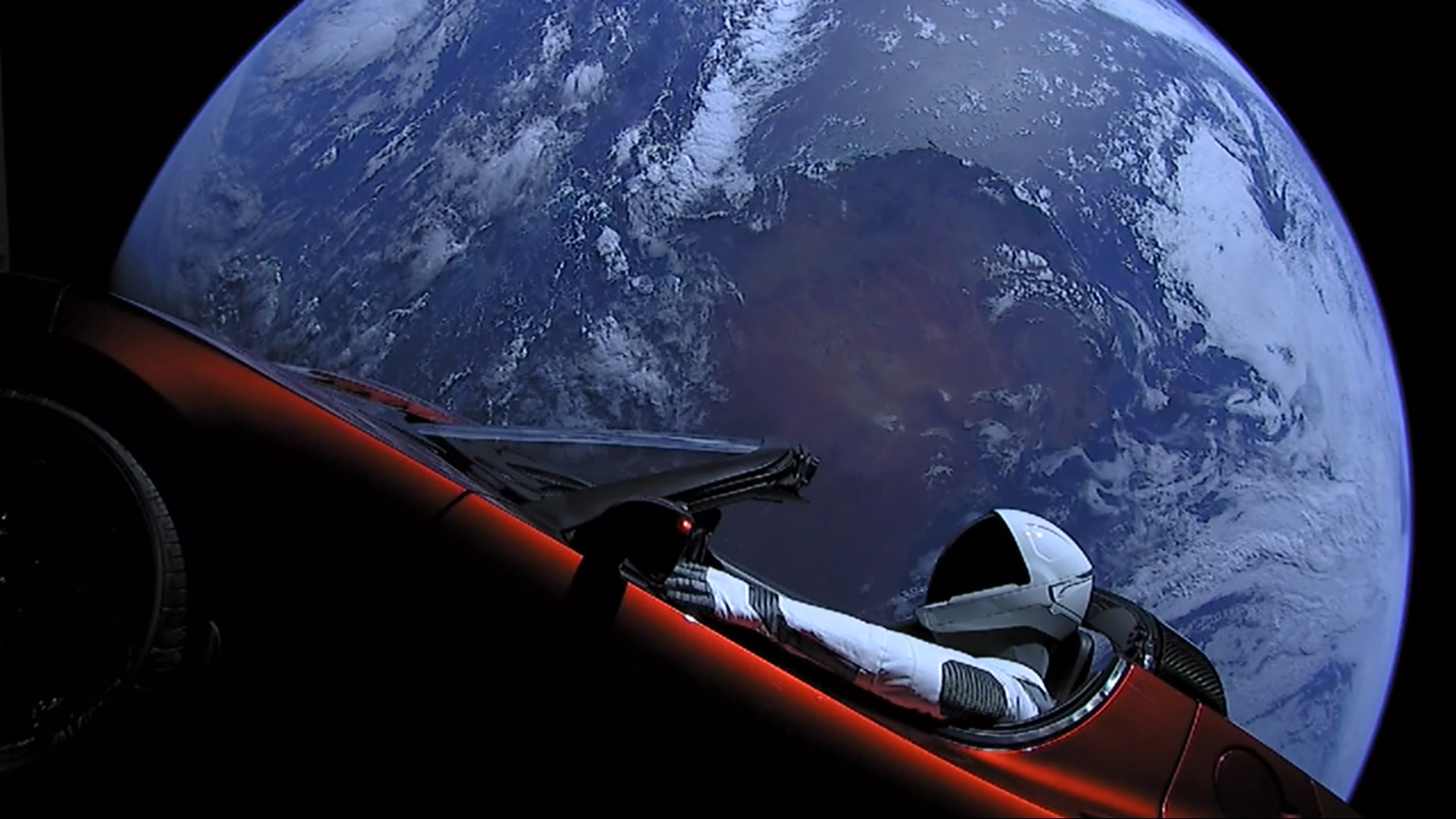The Earth as seen from orbit is the backdrop for what looks like an astronaut driving a red Tesla convertible.