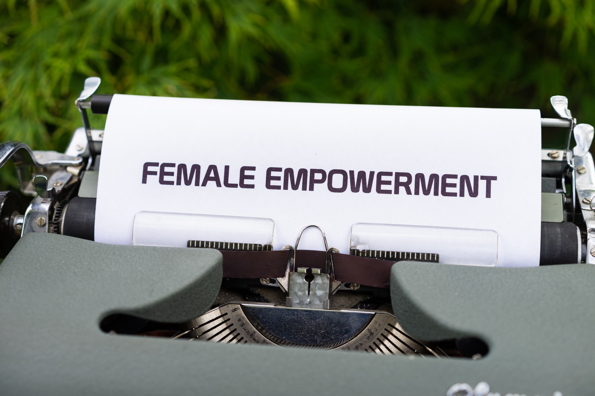 """Typewriter with sheet of paper sticking out, reading """"female empowerment"""" in capital letters"""