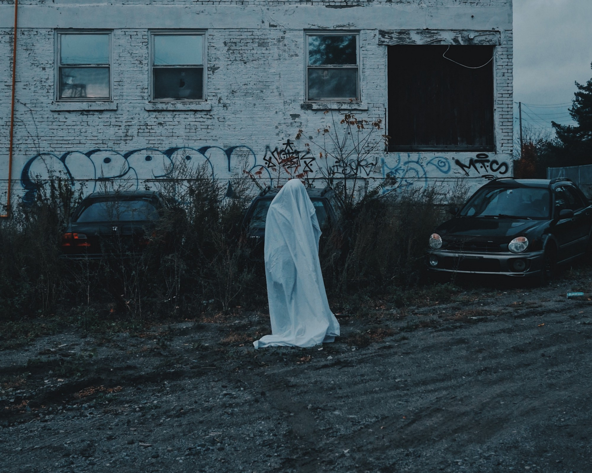 A kid underneath a sheet pretending to be a ghost by an abandoned building