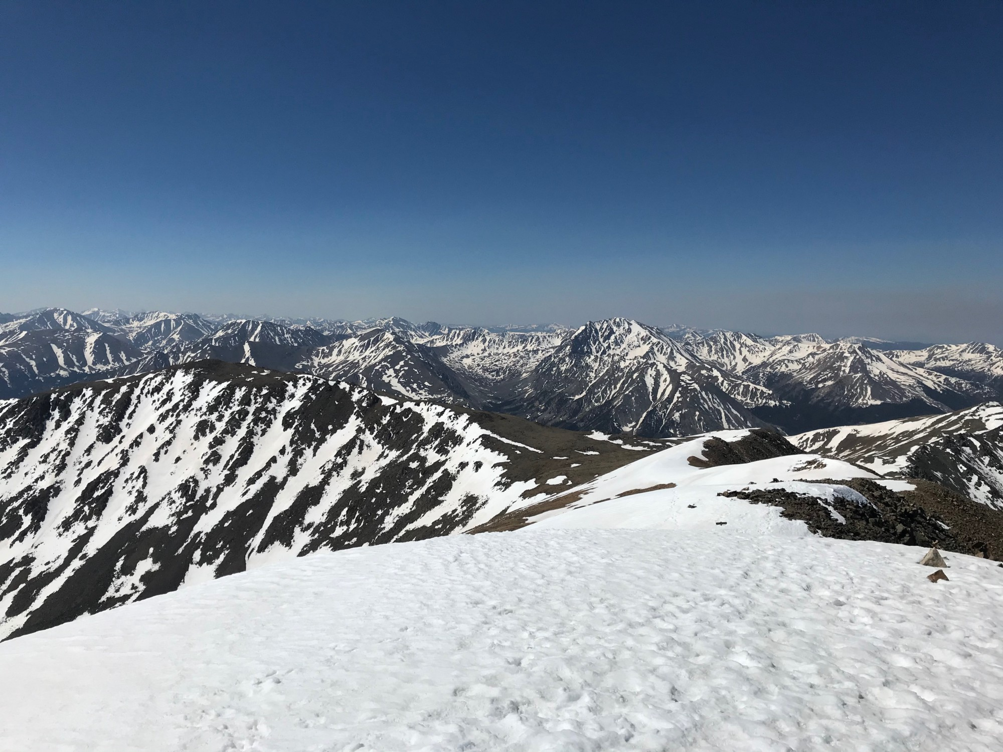 View of snowcapped mountain peaks and blue sky from the top of a mountain.