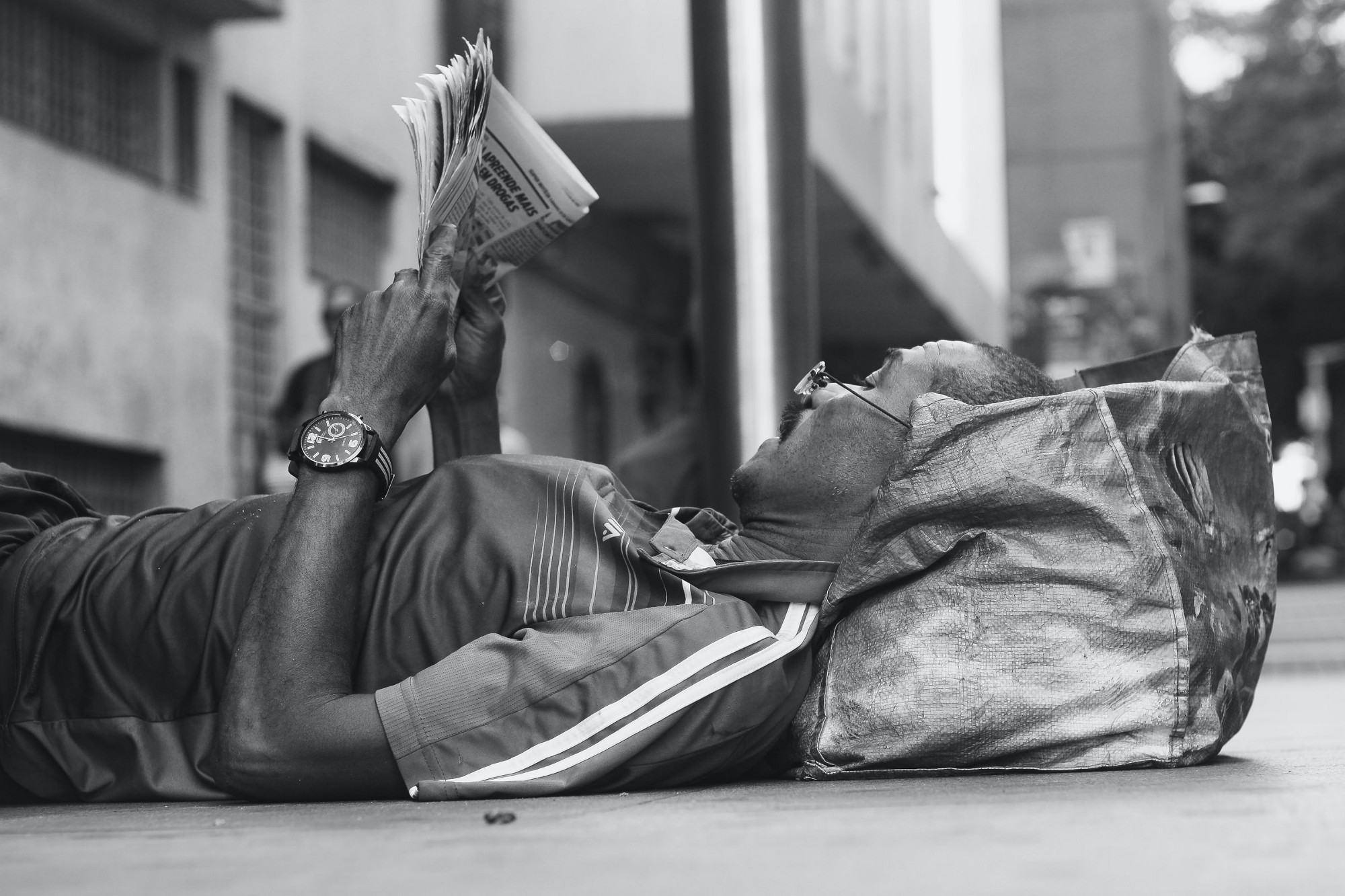 Man lying on sidewalk reading newspaper.