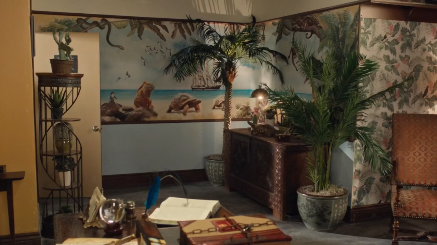 A tropical-themed room with a beach mural, fake palm trees, and wicker furniture