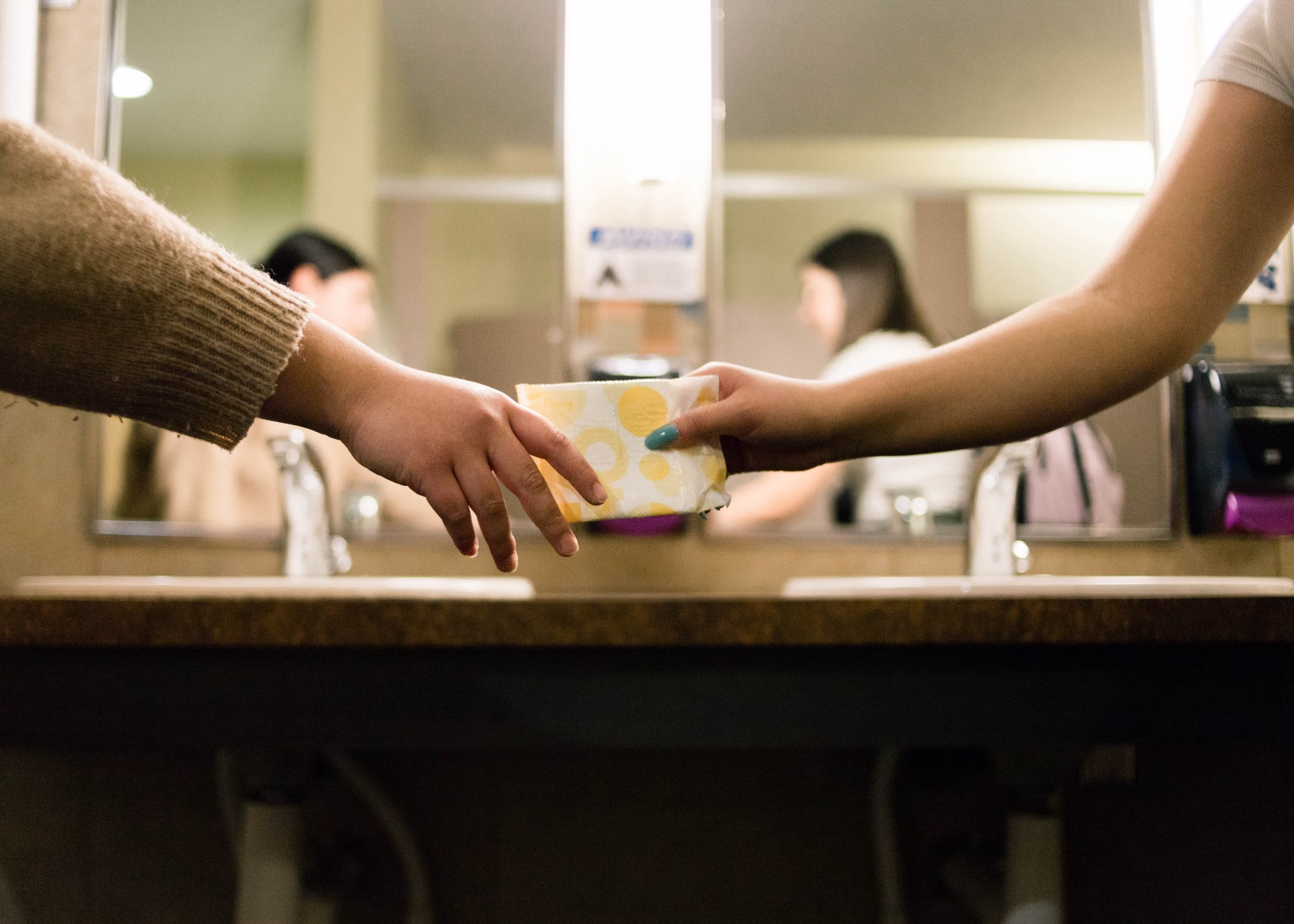 A woman passes a menstrual product to another.
