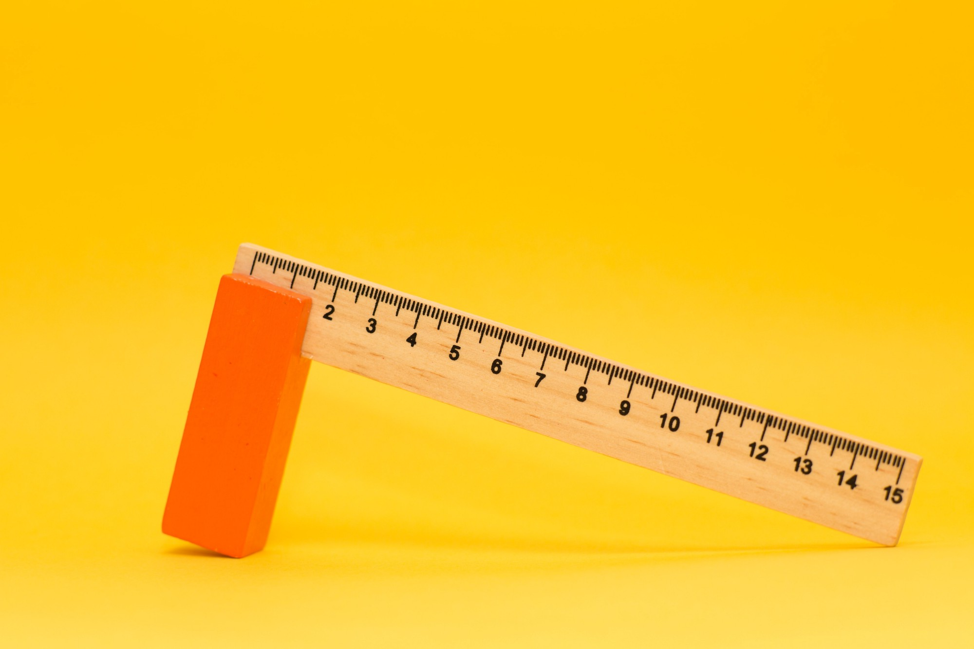 A ruler with one end leaning on an orange block with a yellow background.