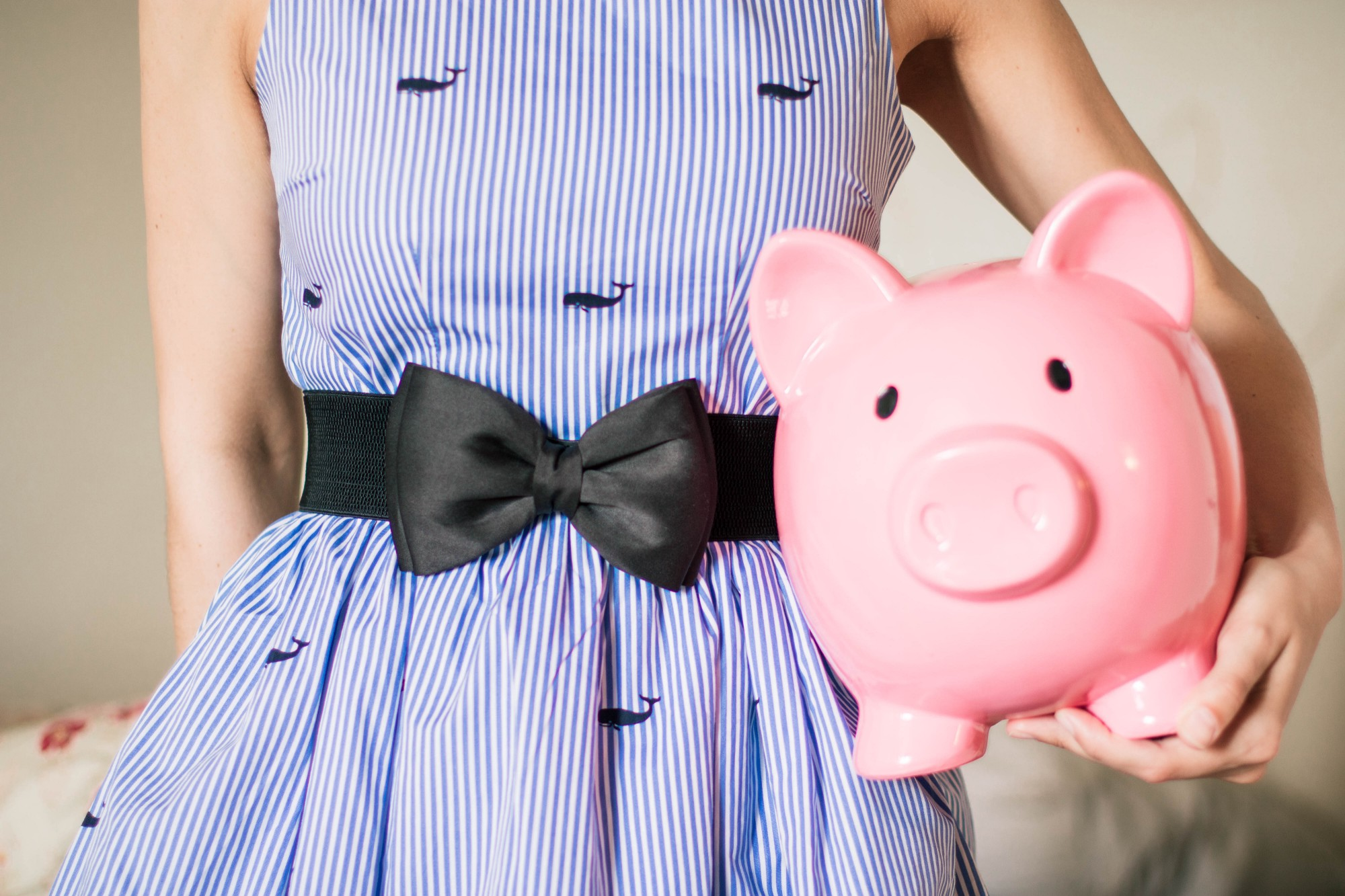A young woman in a blue pinstriped dress with a black bow belt holding a pink piggy coin jar at her hip.