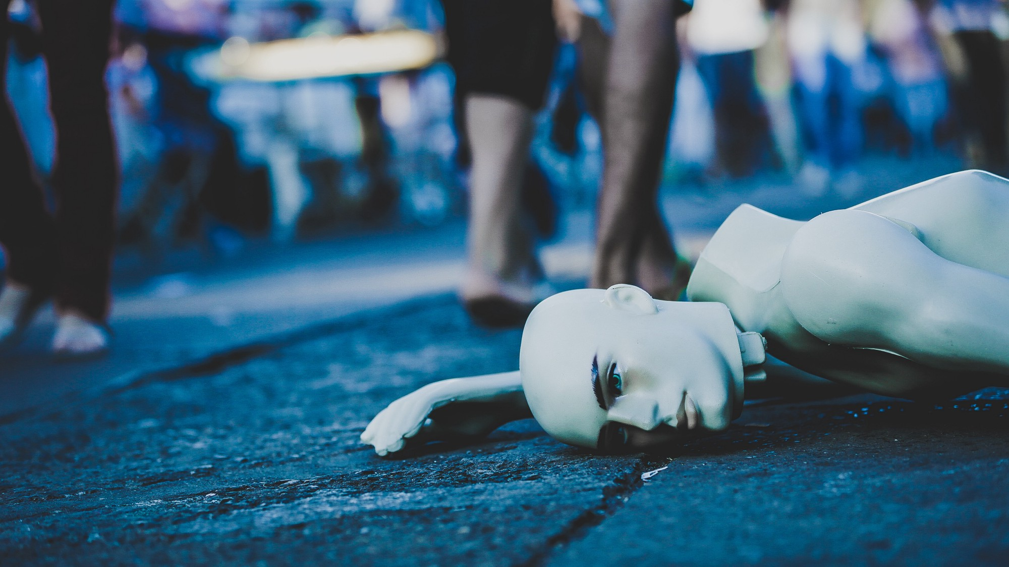 A broken manniquin lays on a sidewalk.