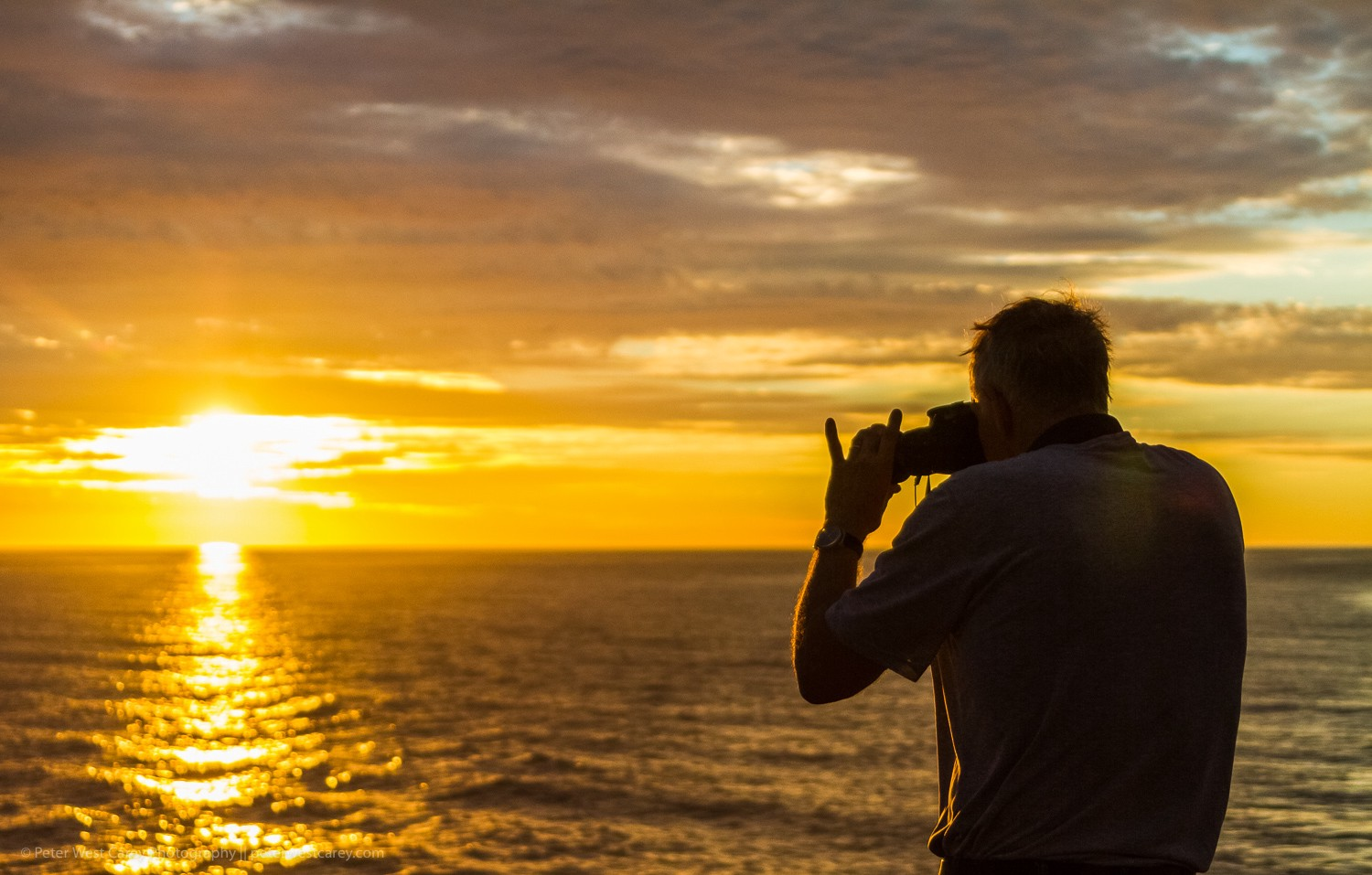 Man taking a photo with his camera. A beuatiful sunset in background.