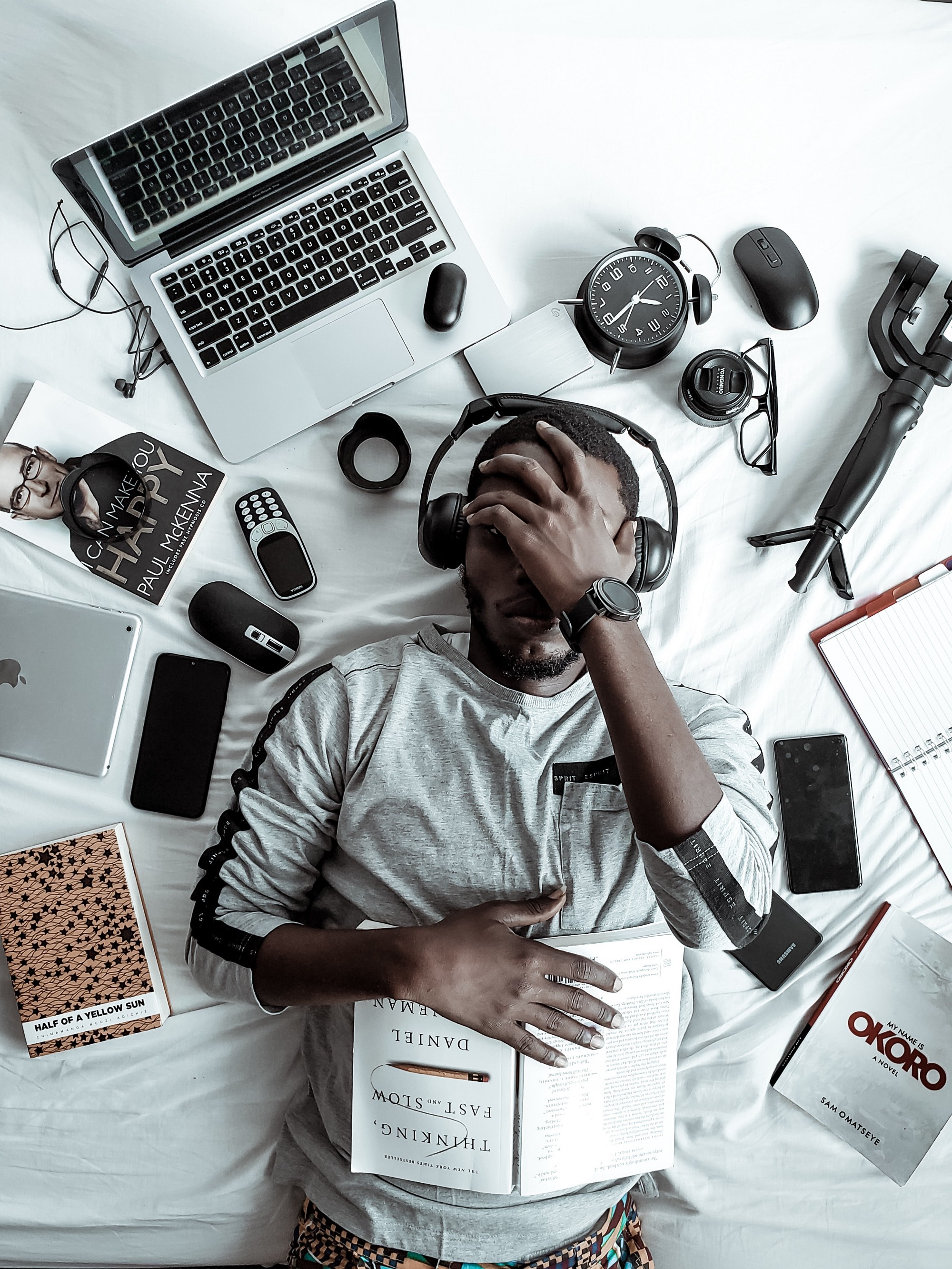 Picture of a man who appears to be overwhelmed, with black headphones on, lyring in a bed, surronded by various books and technology gadgets.