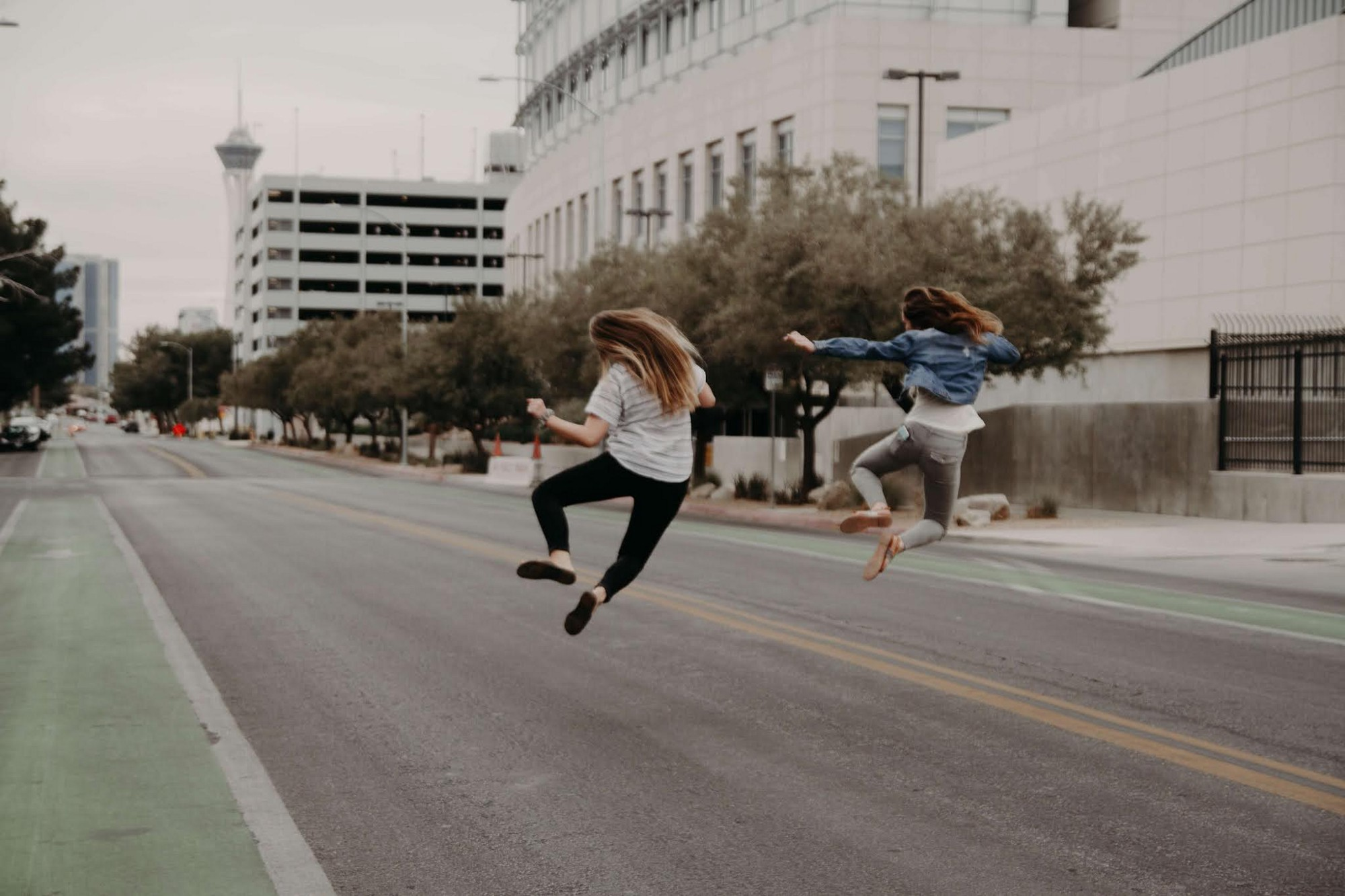 two girls jumping in the air in the middle of city road, they look like they succeeded