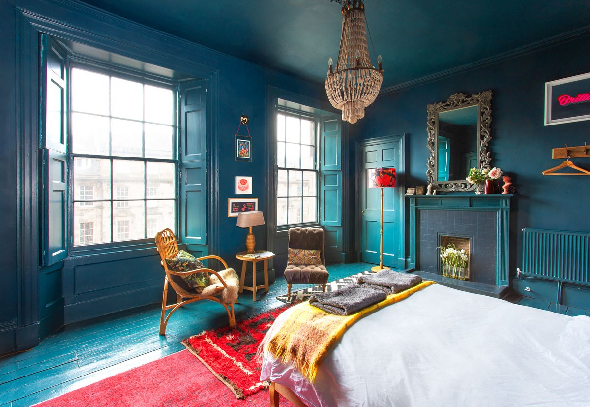 A wood-paneled bedroom painted in various shades of deep blue.