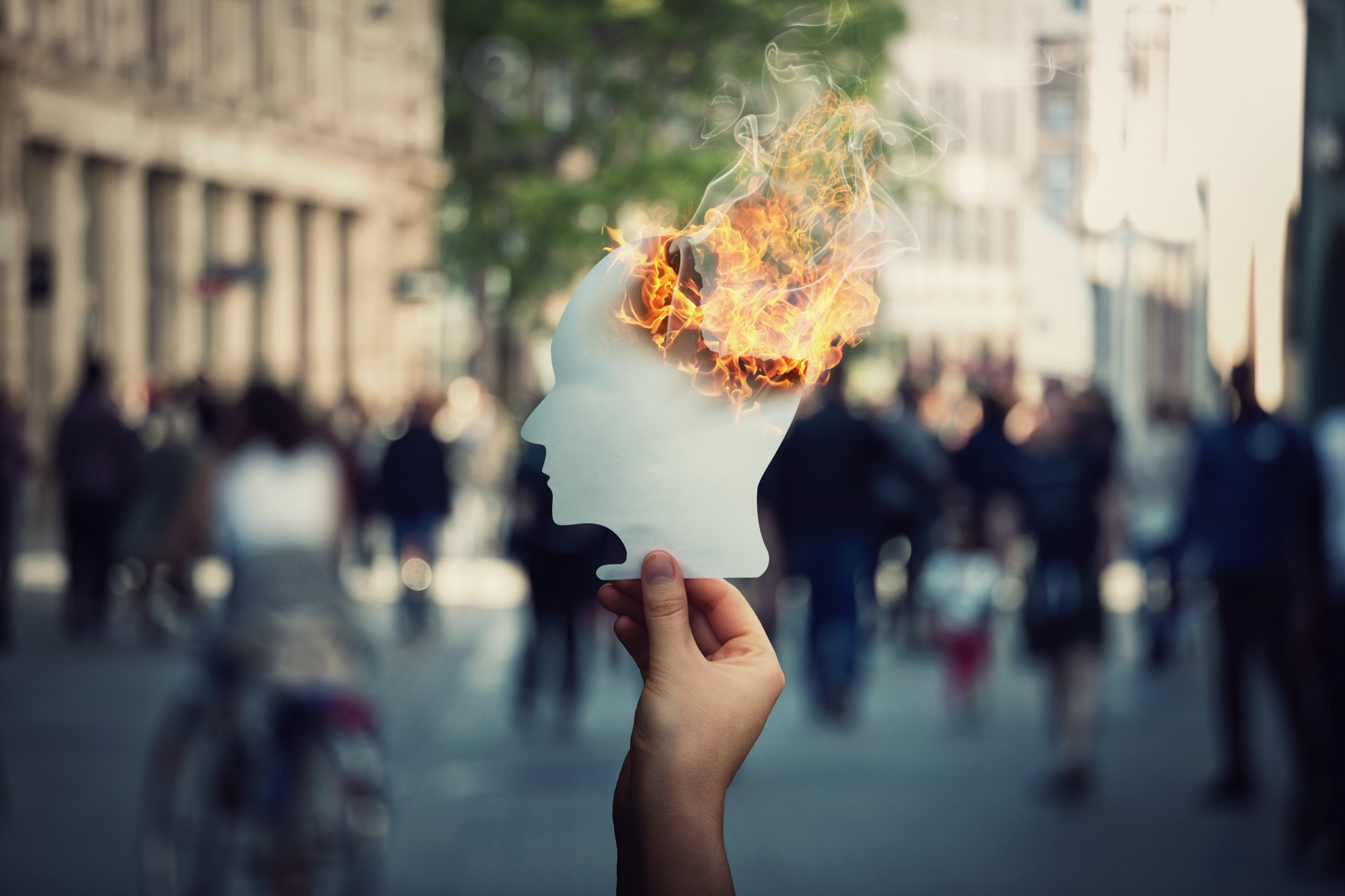 Burnout and stress concept as person hand holds a burning, human head shaped, paper sheet on a crowded street.