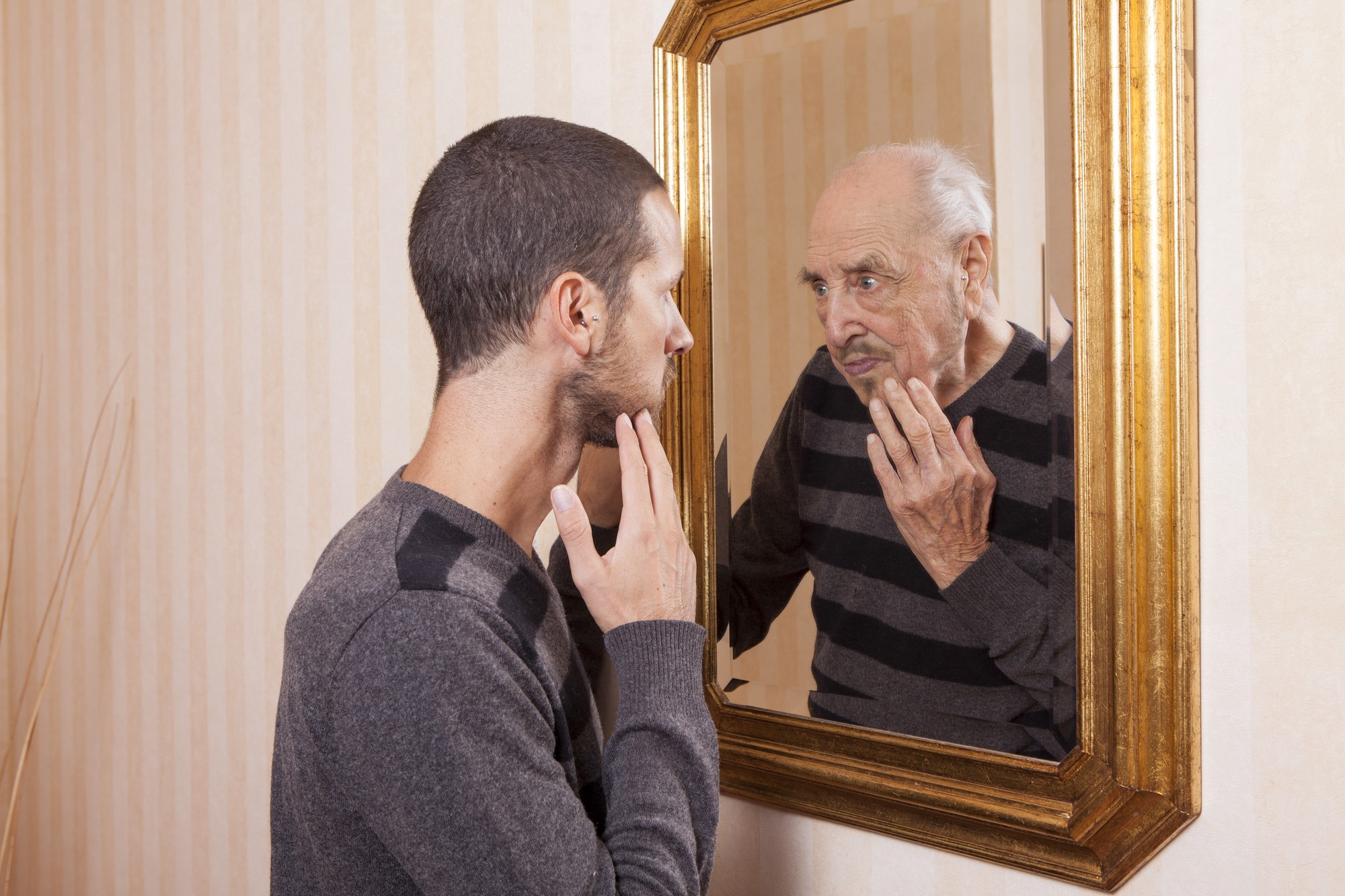 young man looking at reflection of older man in mirror