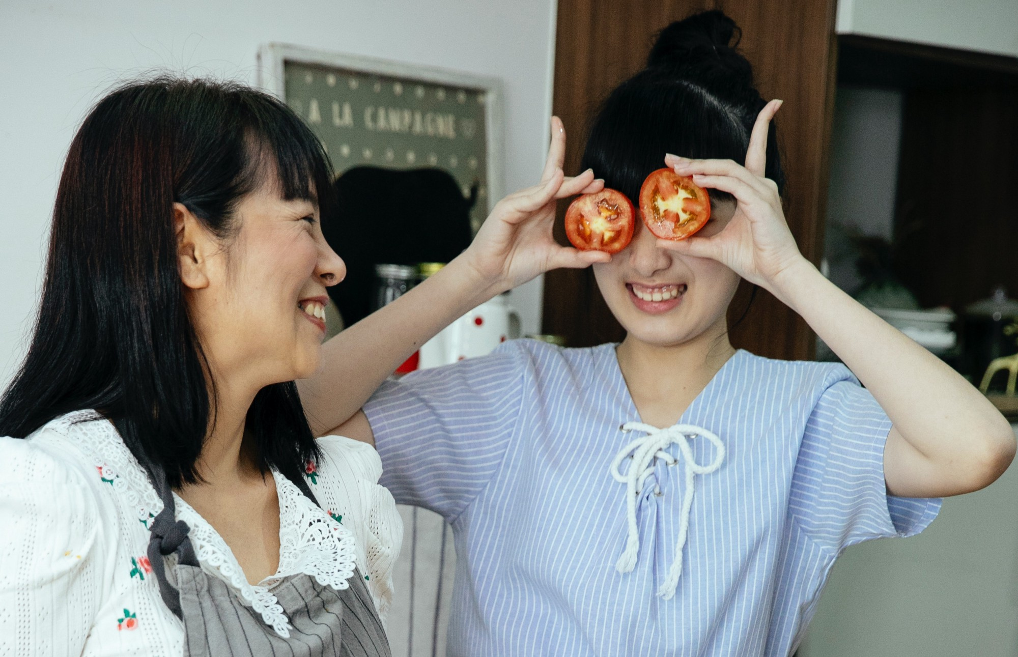 girl fun. She is take the halves of tomato on her eyes.