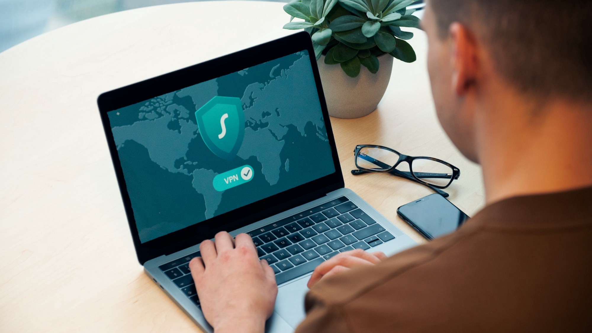 Man looking at laptop with security symbol on the screen.