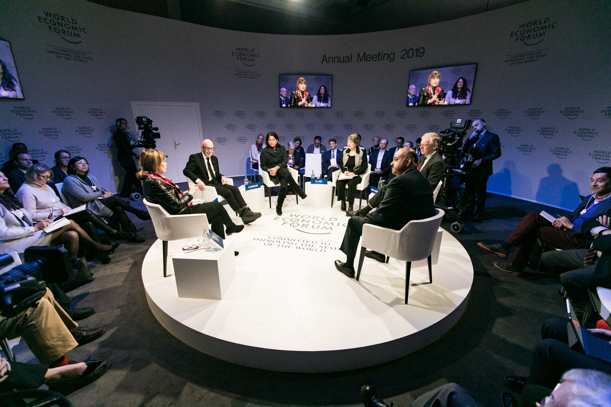 People sitting and talking on a round stage with an audience.