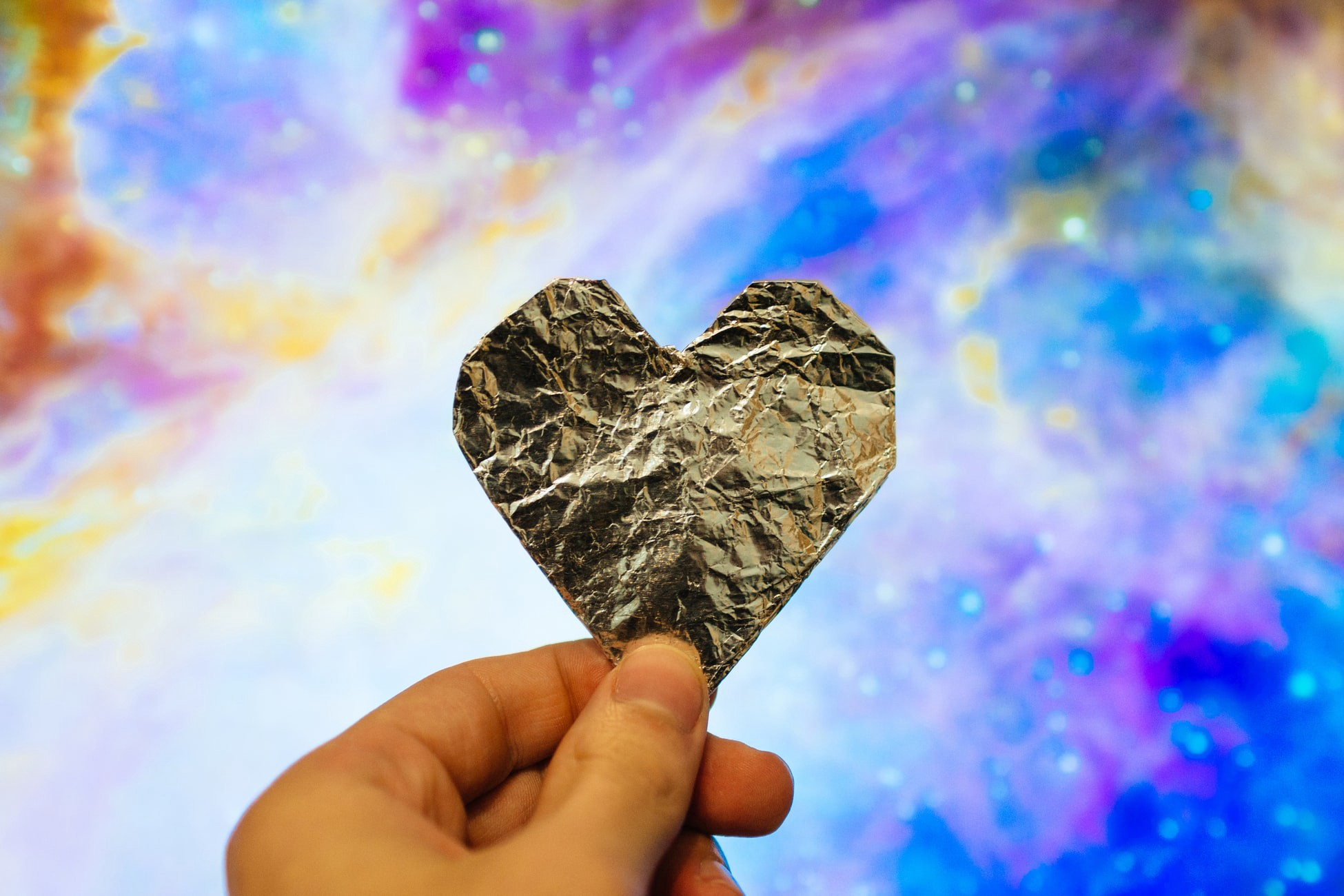 A hand holding up a heart-shaped piece of wrinkled gold foil against a pink, purple, blue, and gold background