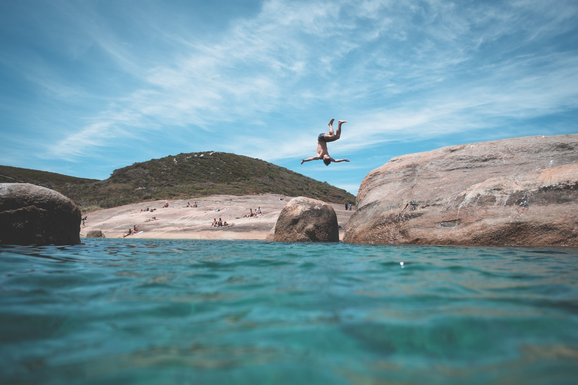 man somersaulting into the ocean