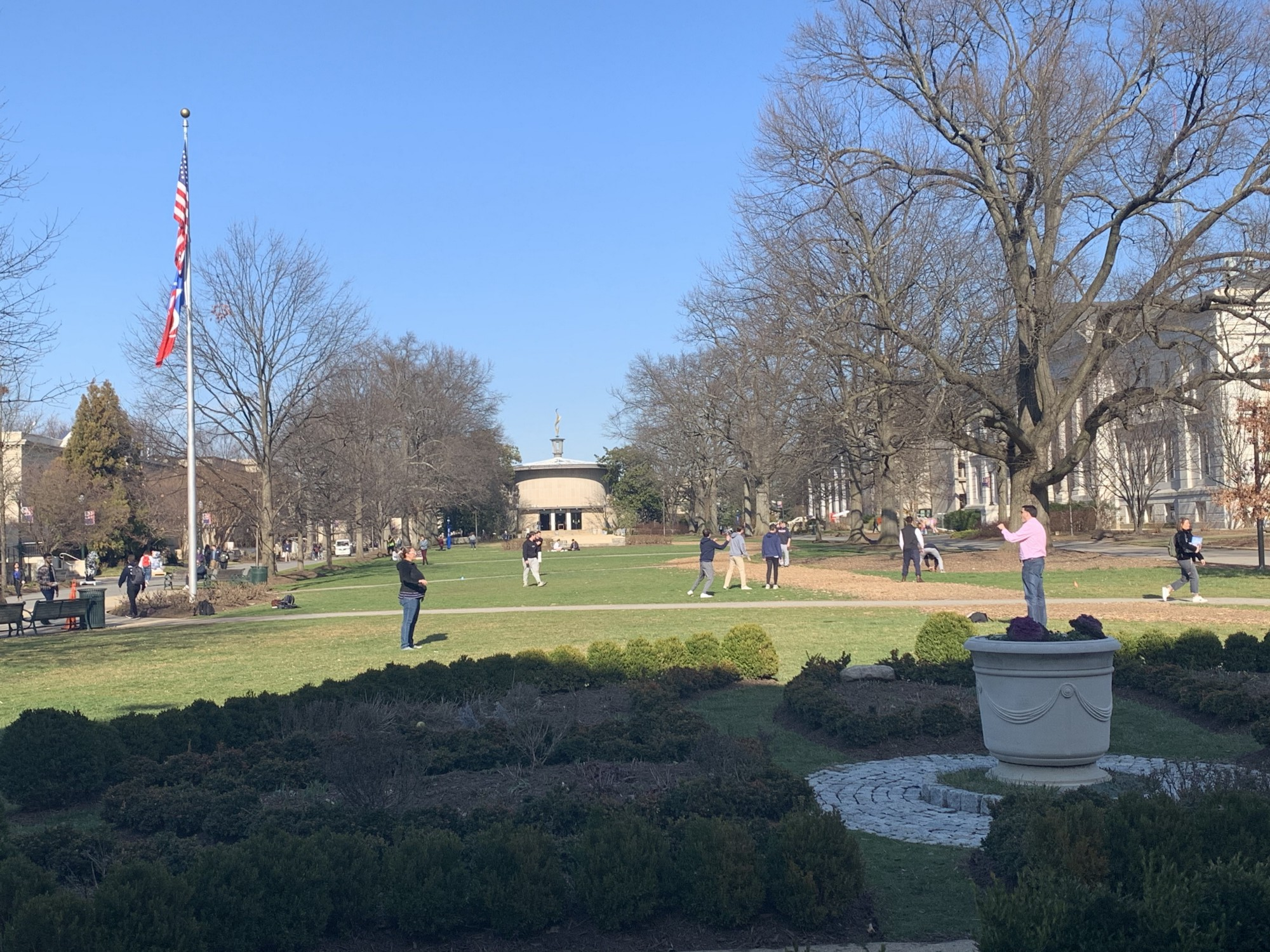 American University Quad with several people walking and playing catch on a pre-spring, sunny day in February of 2020.