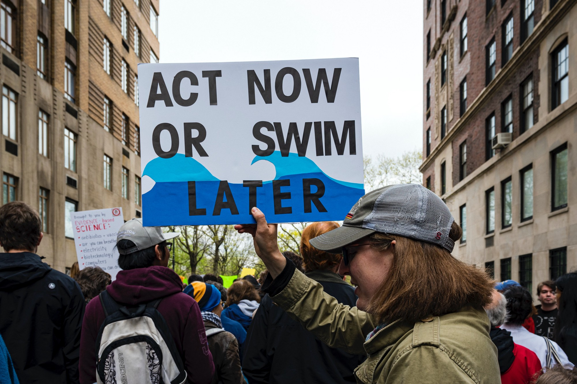 "Protestor with sign that reads: ""Act Now or Swim Later"""