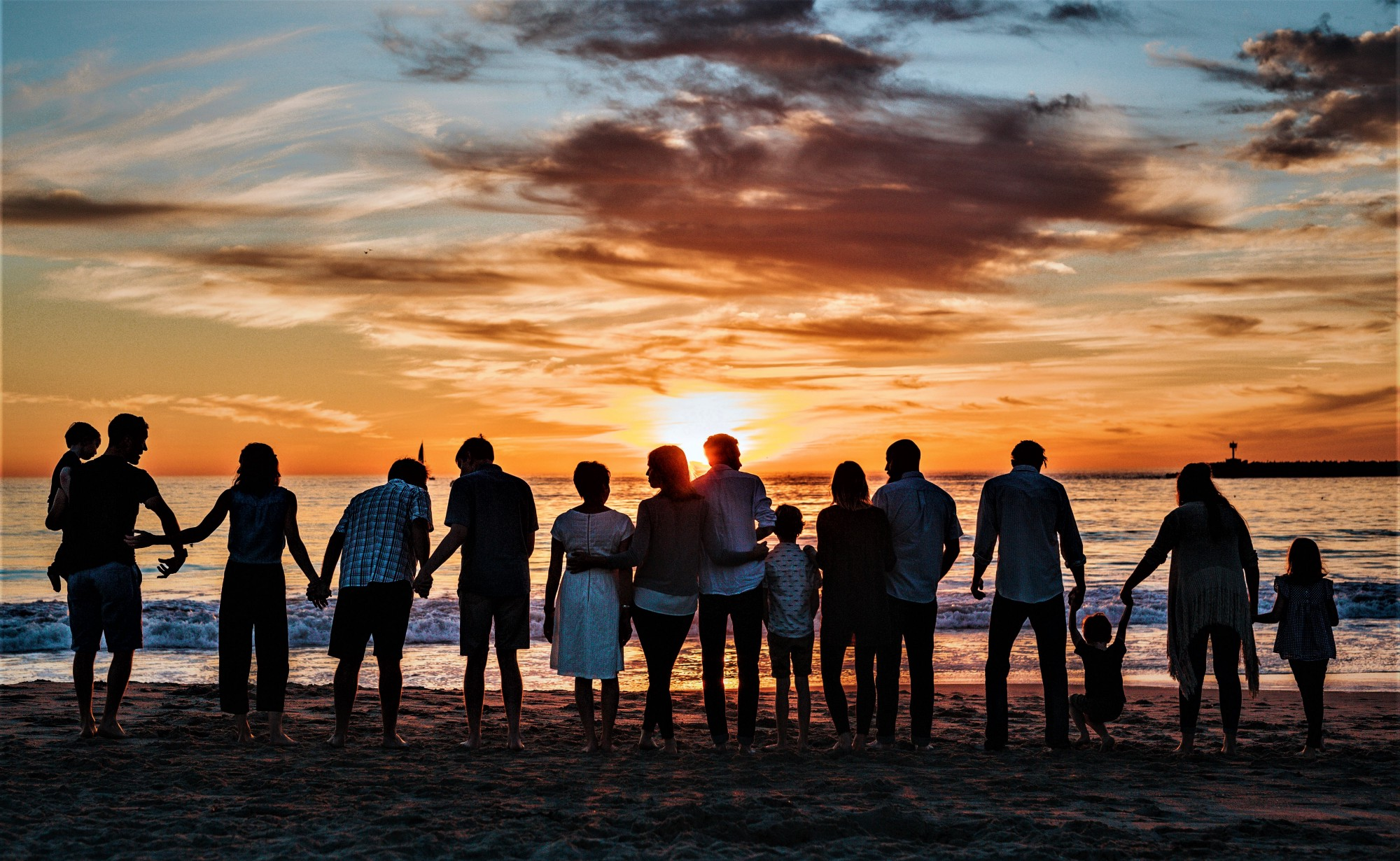 Silhouette of group of people on the beach looking out toward the ocean and colorful sunset