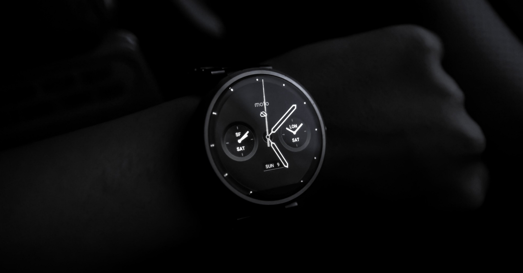 A Moto brand smartwatch shot in the dark, highlighting analogue clock with metrics like notifications & weather on watch face