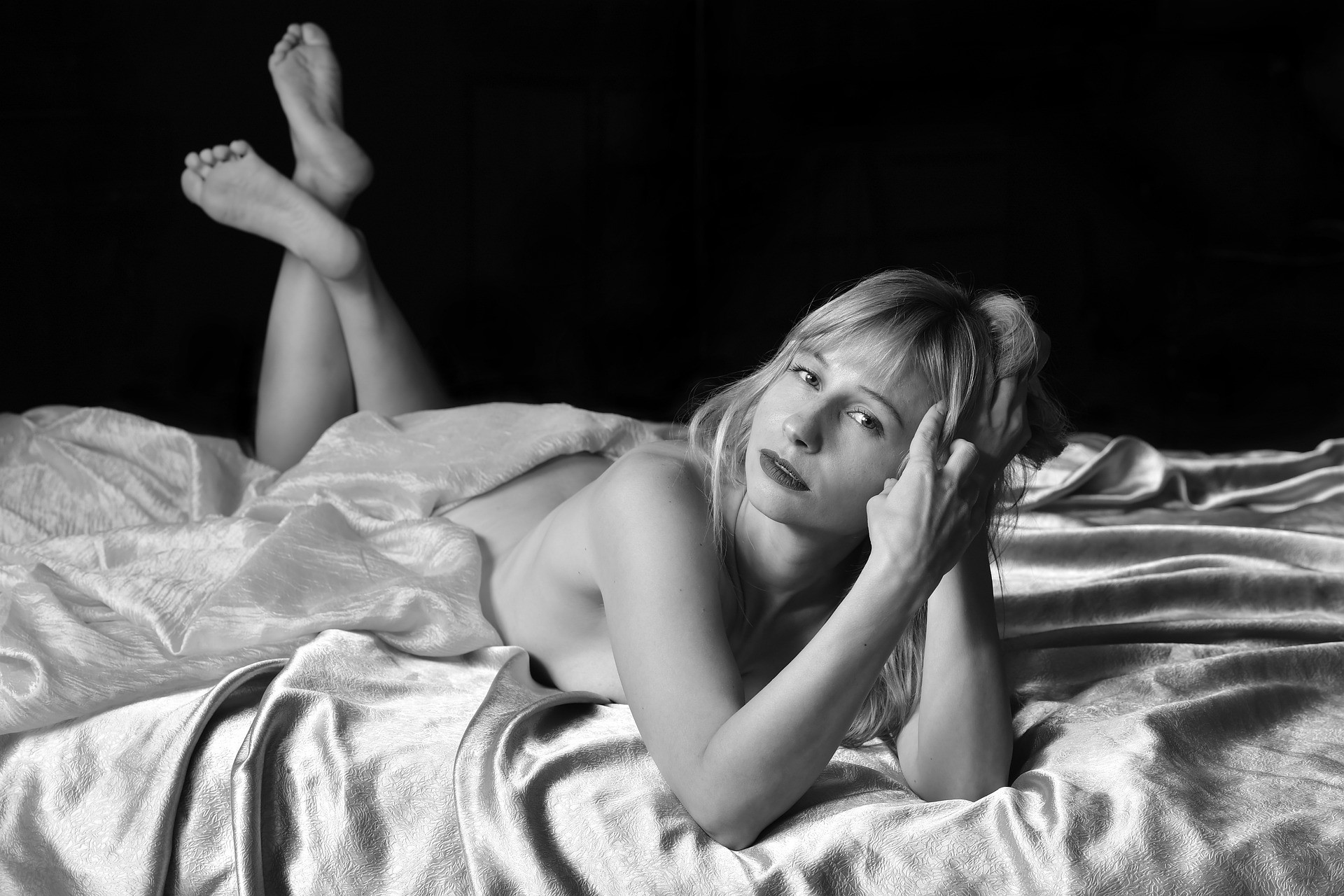 Photo of naked blonde woman lying on her stomach on a bed, feet raised behind her, buttocks covered by sheet