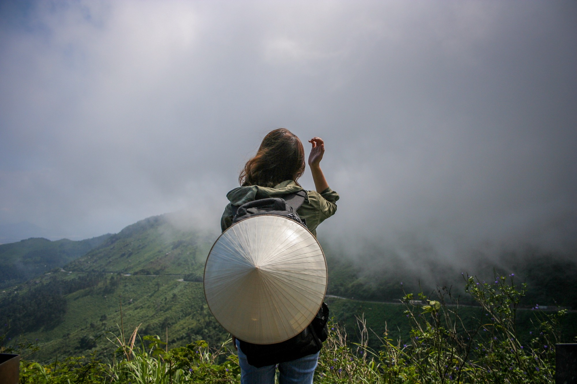 Someone looking at a scenic landscape on a cloudy day, with a rice hat attached to the back