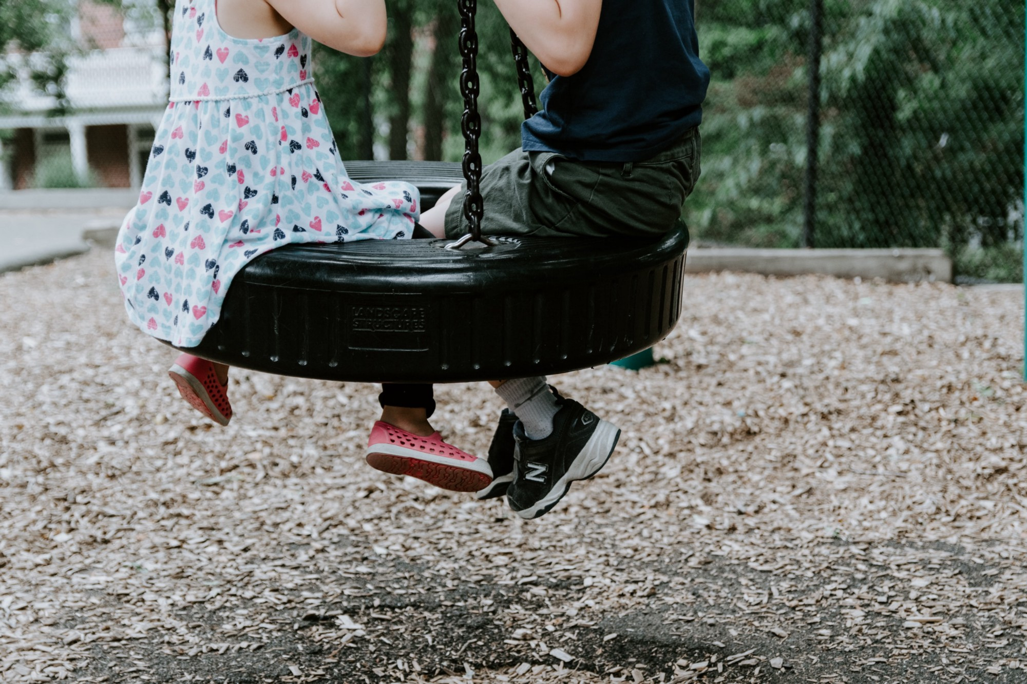 A close-up shot of two children on a tire swing. One is wearing a patterned dress and pink shoes. The other is wearing a dark navy shirt, dark green shorts, and black shoes. They are on a playground with wood chips on the ground and trees in the background