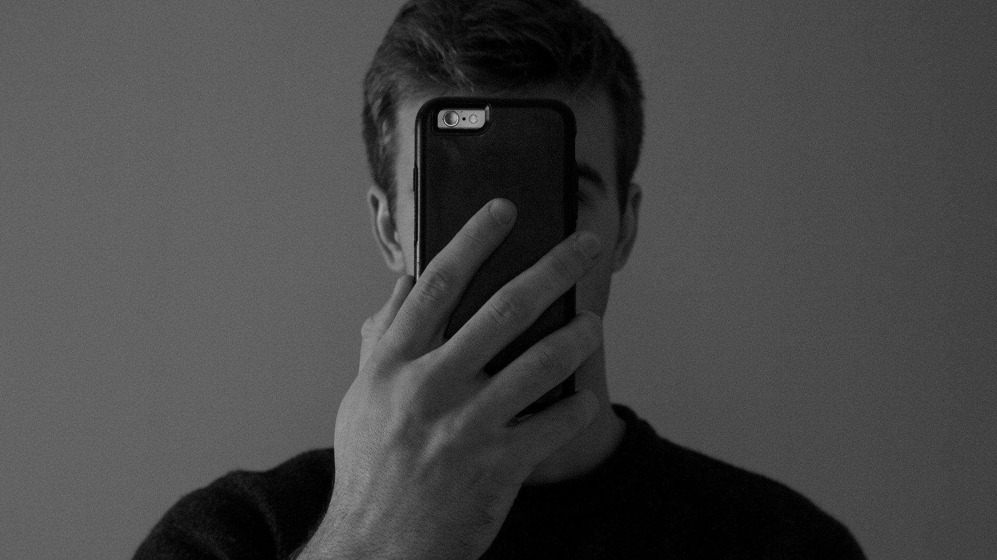 A man scrolls on a phone covering his face