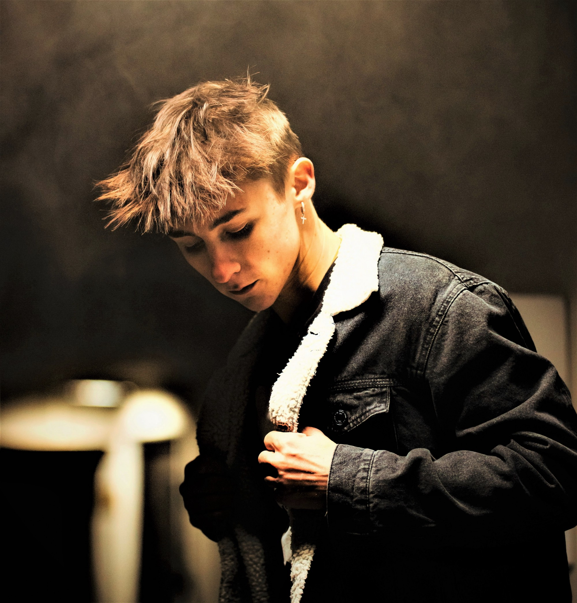 somber young man with blonde hair wearing jacket with white collar
