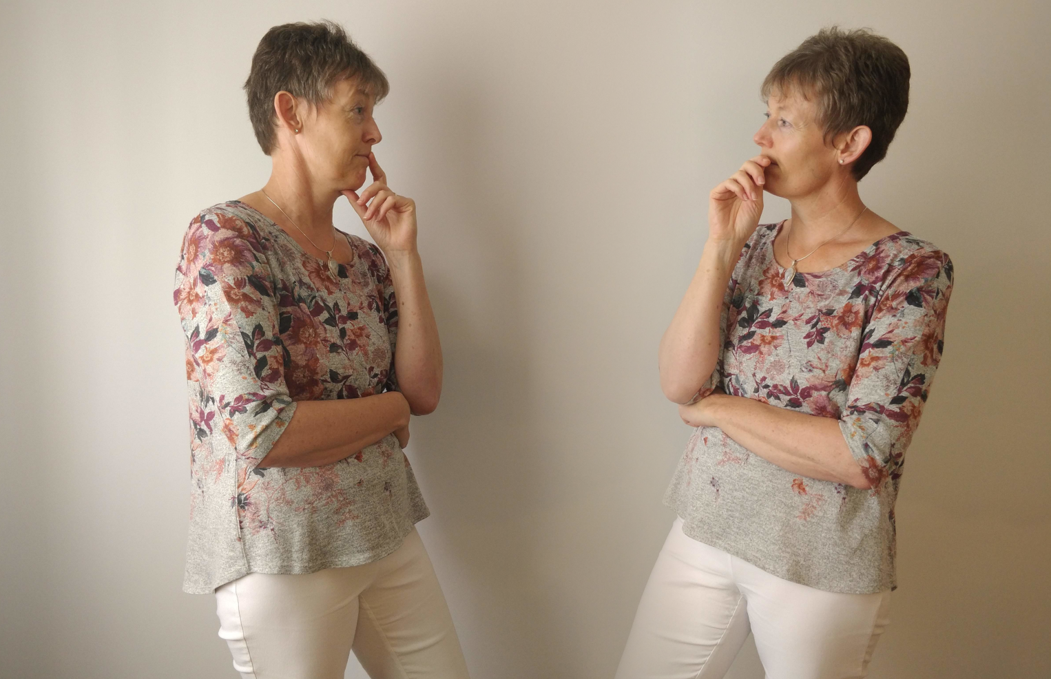 Two identical women stand looking at each other with puzzled expressions on their faces. The women are wearing white pants and grey tops with a floral pattern.