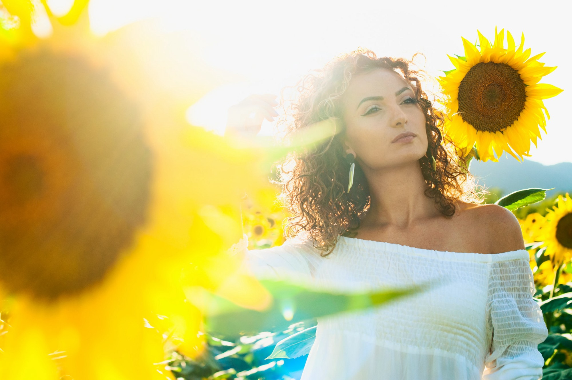 Woman in white off shoulder top among sunflowers