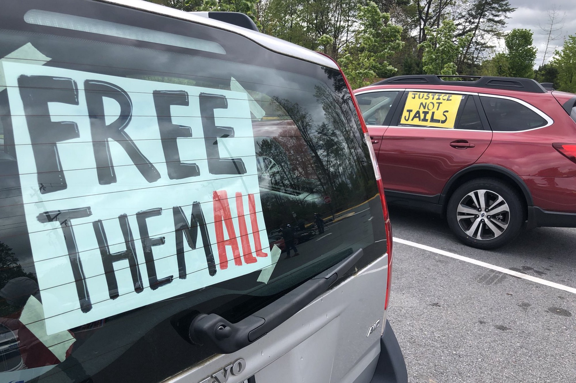 Two cars with signs. One says free them all and the other says justice not jails