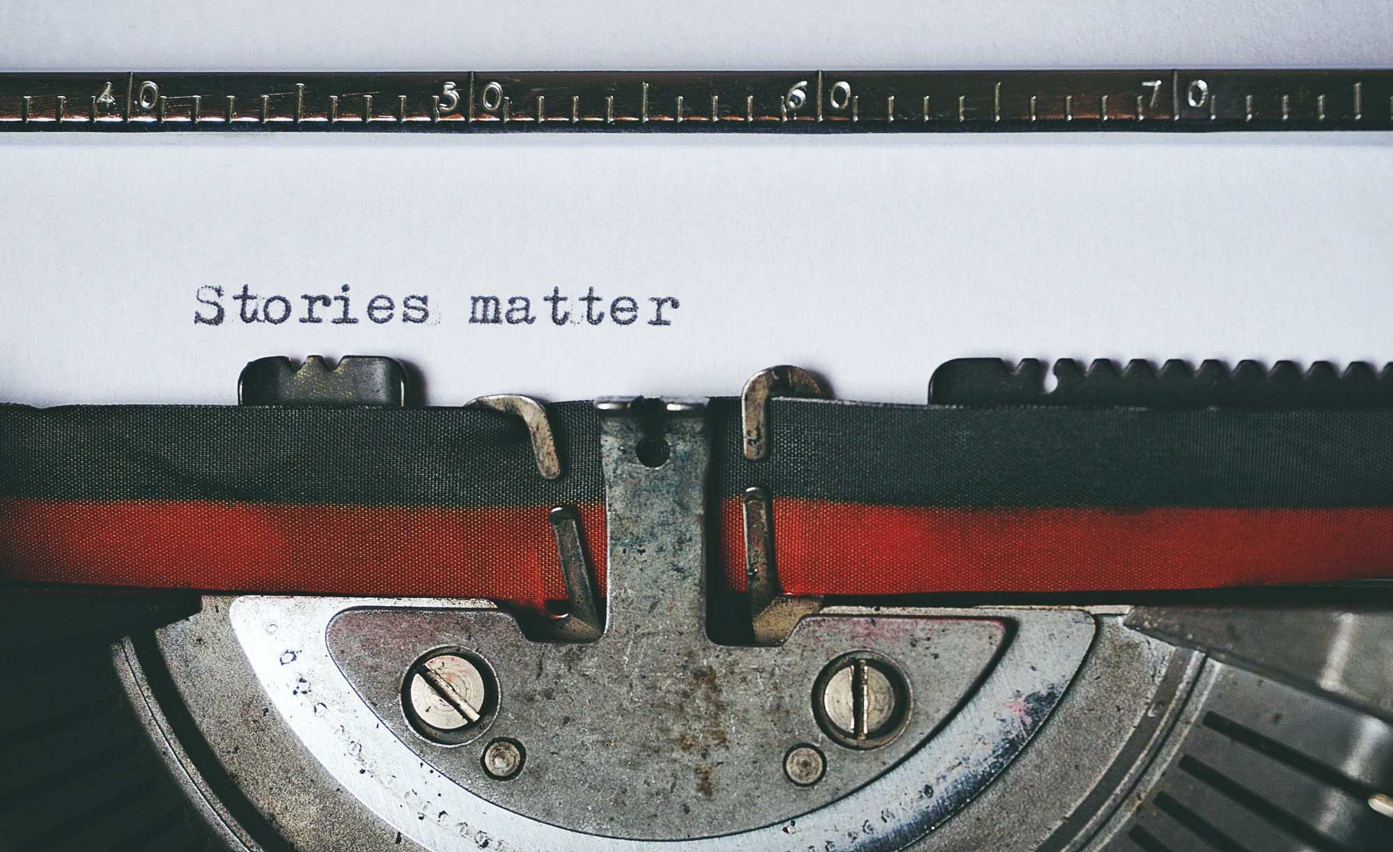"black & red typewriter with ""stories matter"" written on paper"