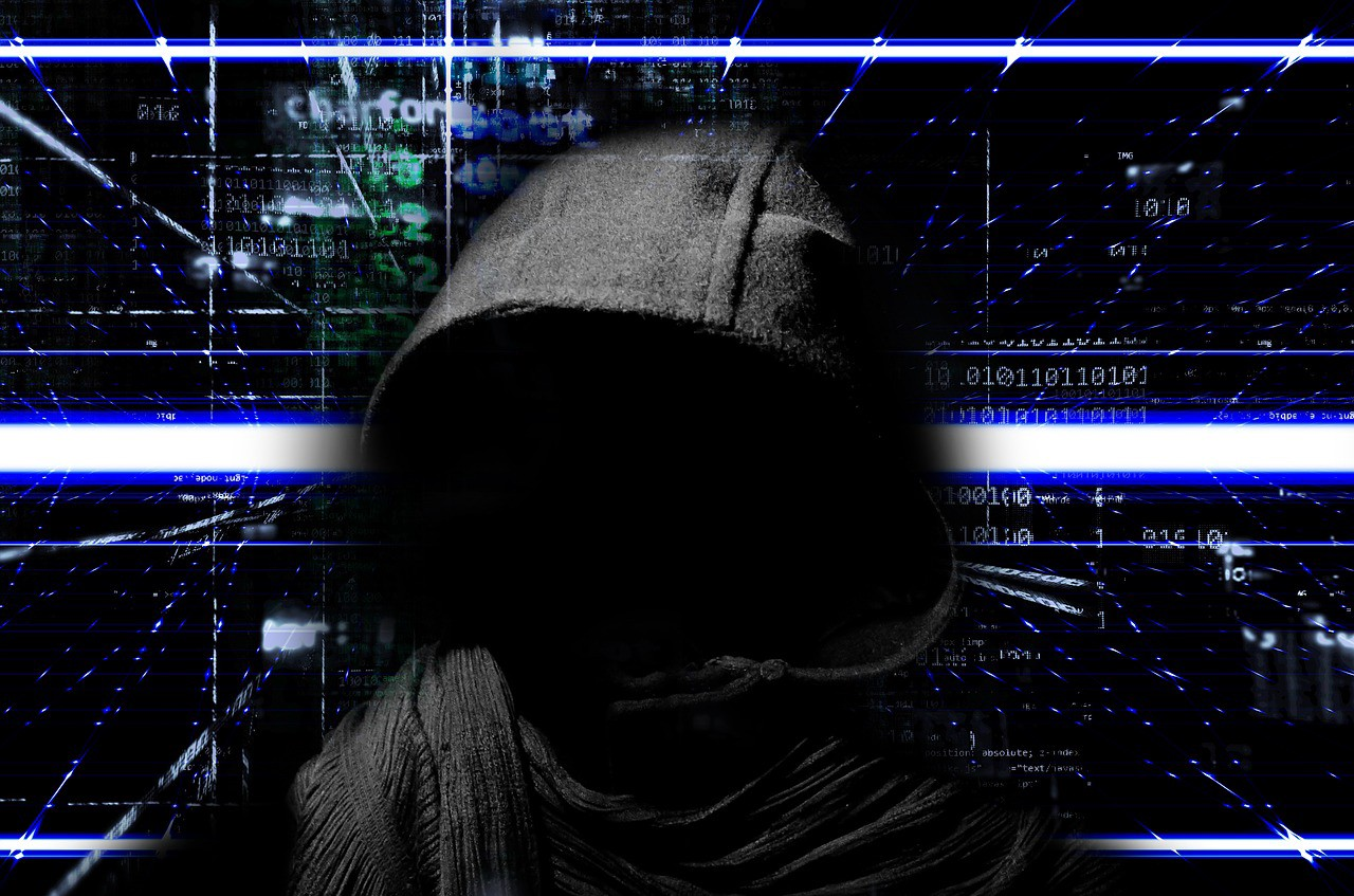 A scary-looking hooded man in front of an electronic display.