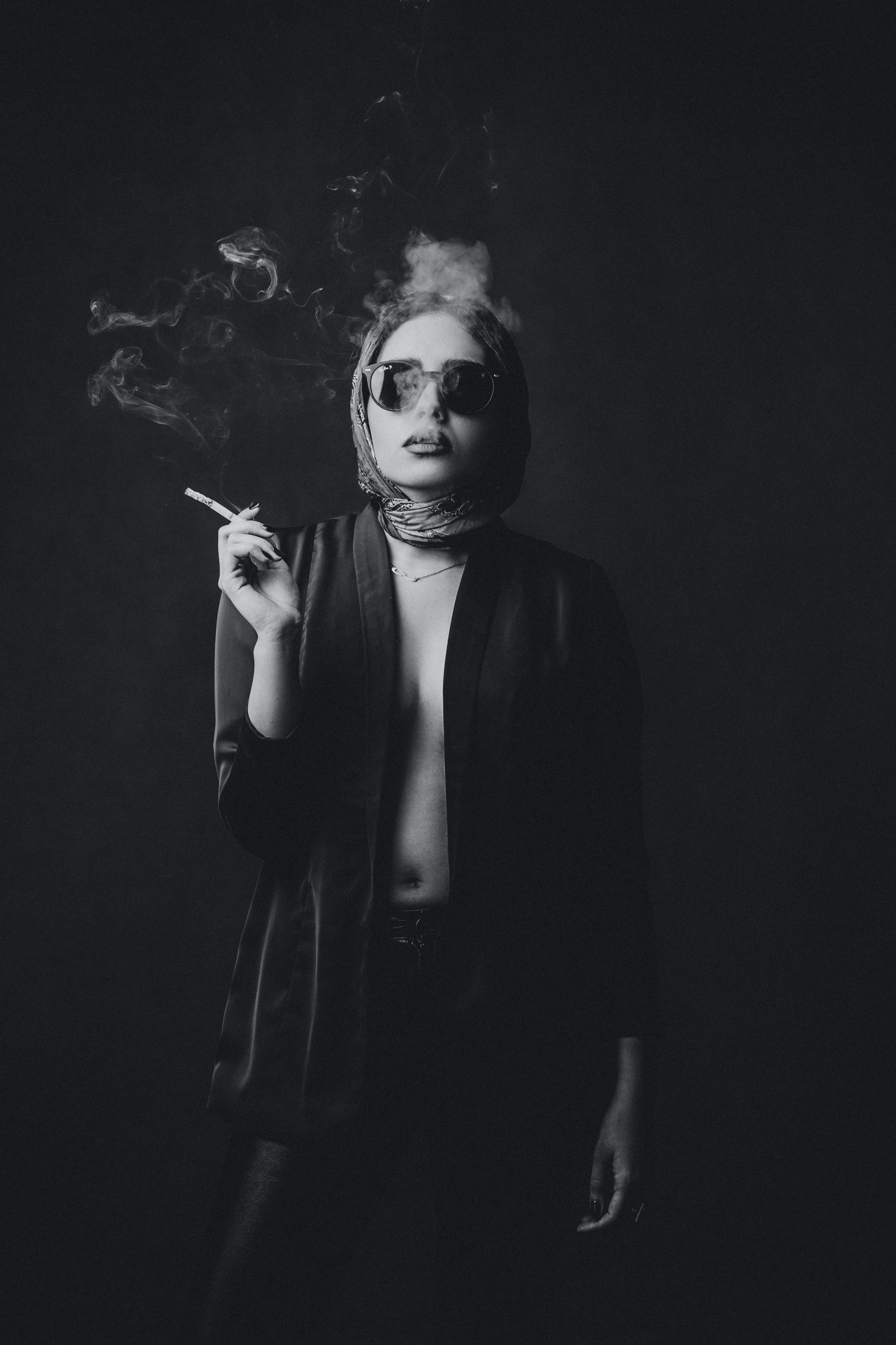Black and white photo of stylish woman partially showing skin, smoking a cigarette