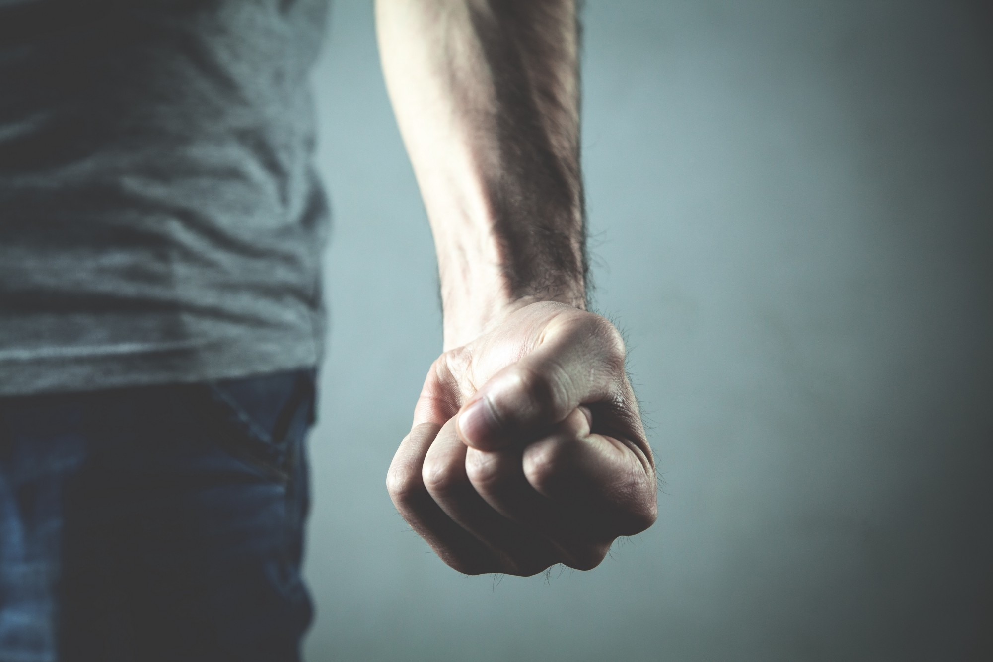 This is an image of a man standing with his left arm extended down and his left fist clenched in anger. The anger shows in the bulging veins of his arm.