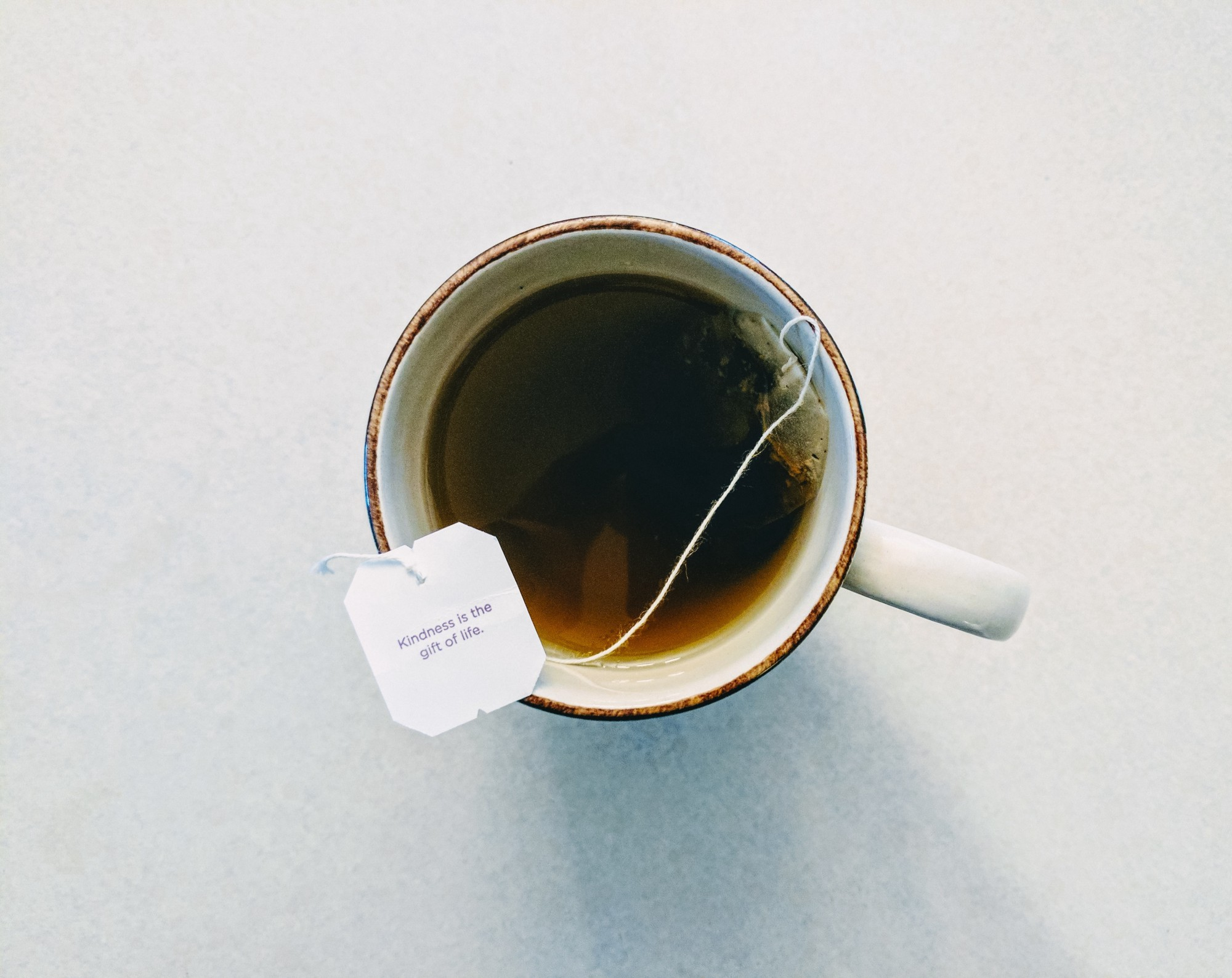 A camera looks down on a cup of black tea. A tag on the teabag reads 'Kindness is the gift of life.'