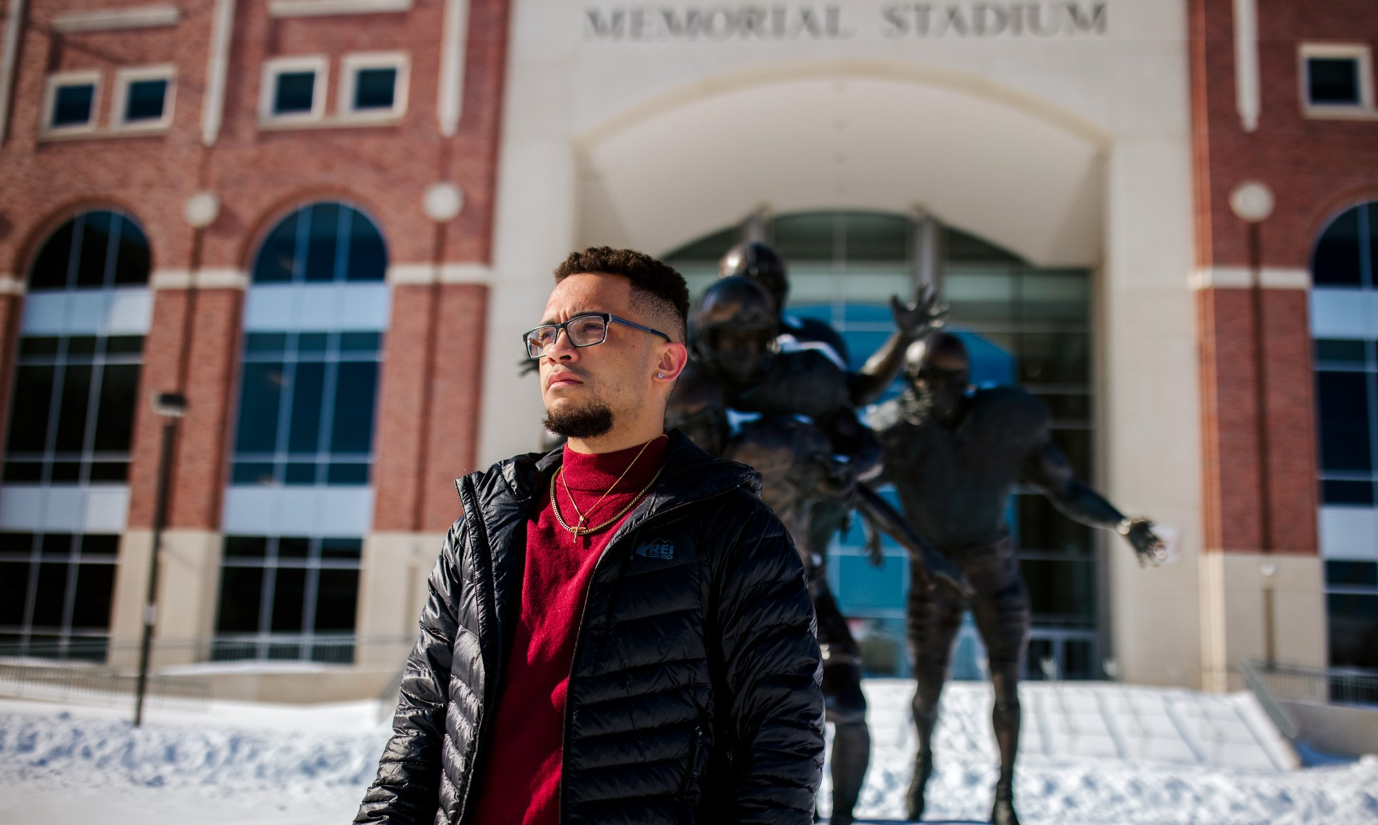 Drake Keeler stands in front of Memorial Stadium looking off to the left