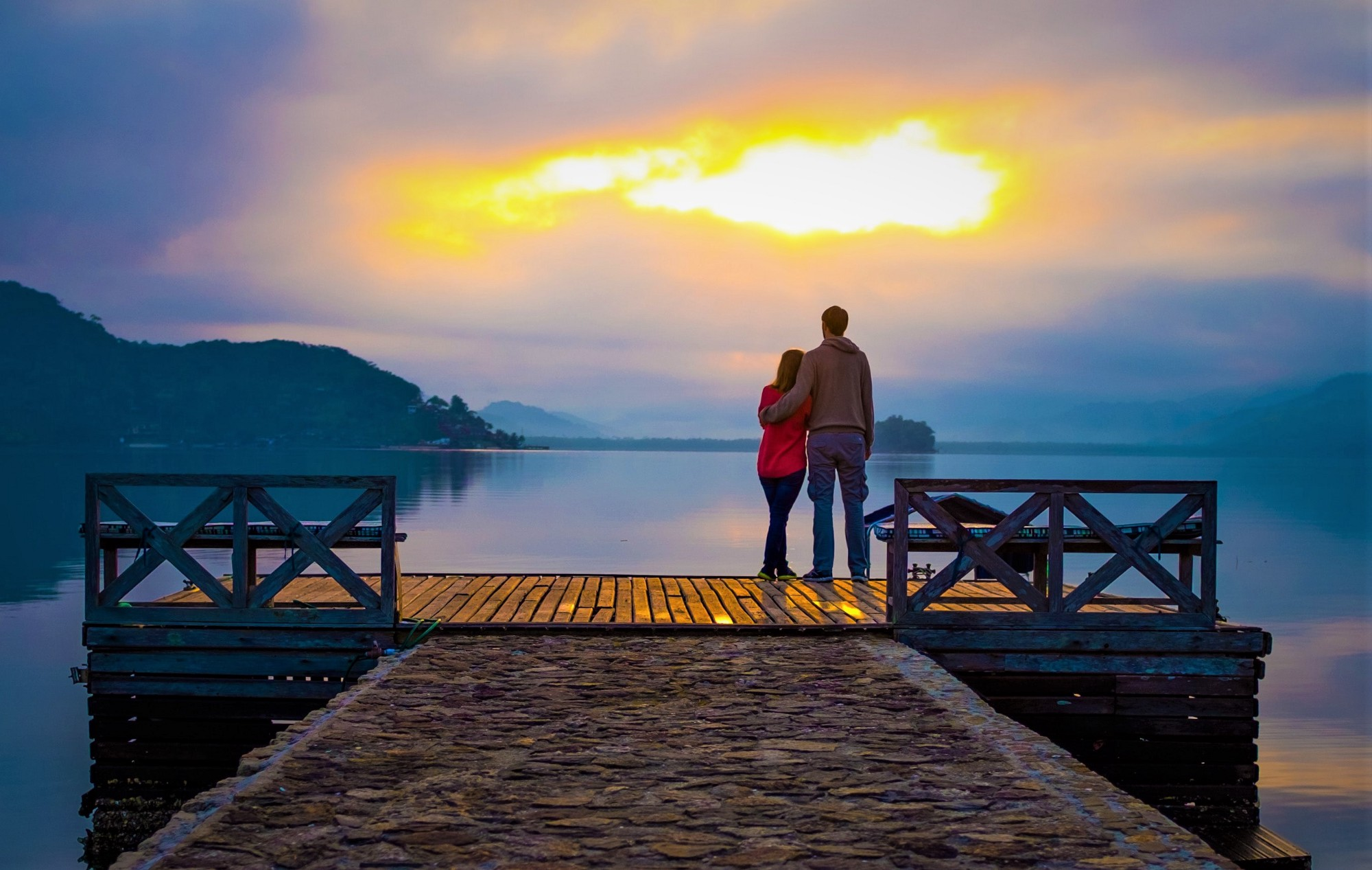 man and woman standing on end of pier looking out over ocean and sunset
