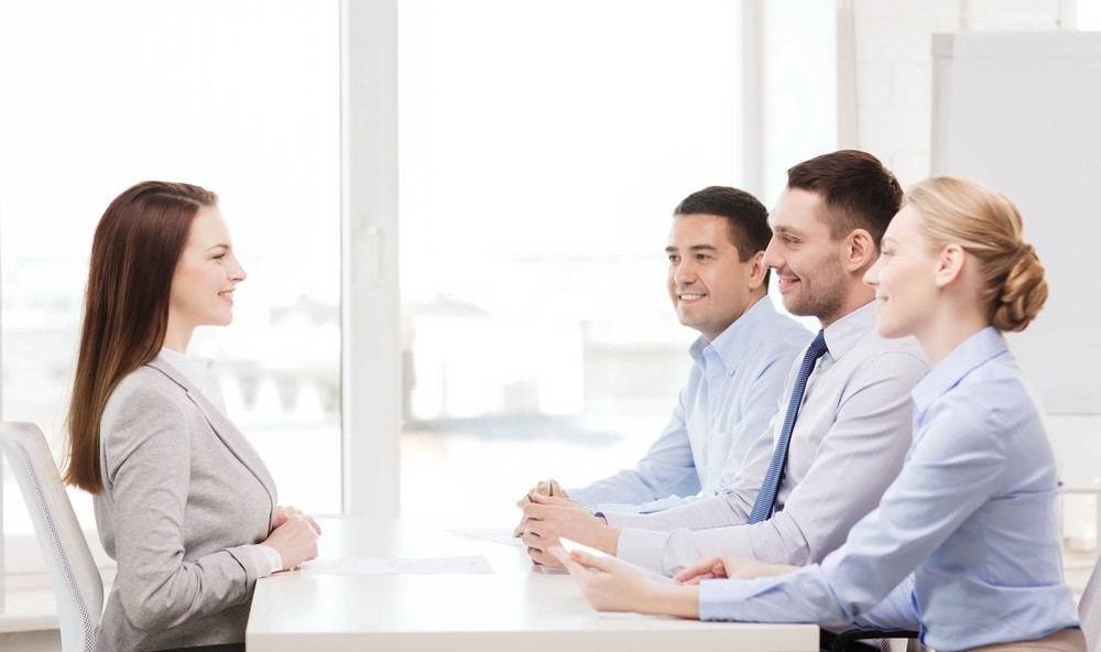 Job candidate at a table interviewing with three employees