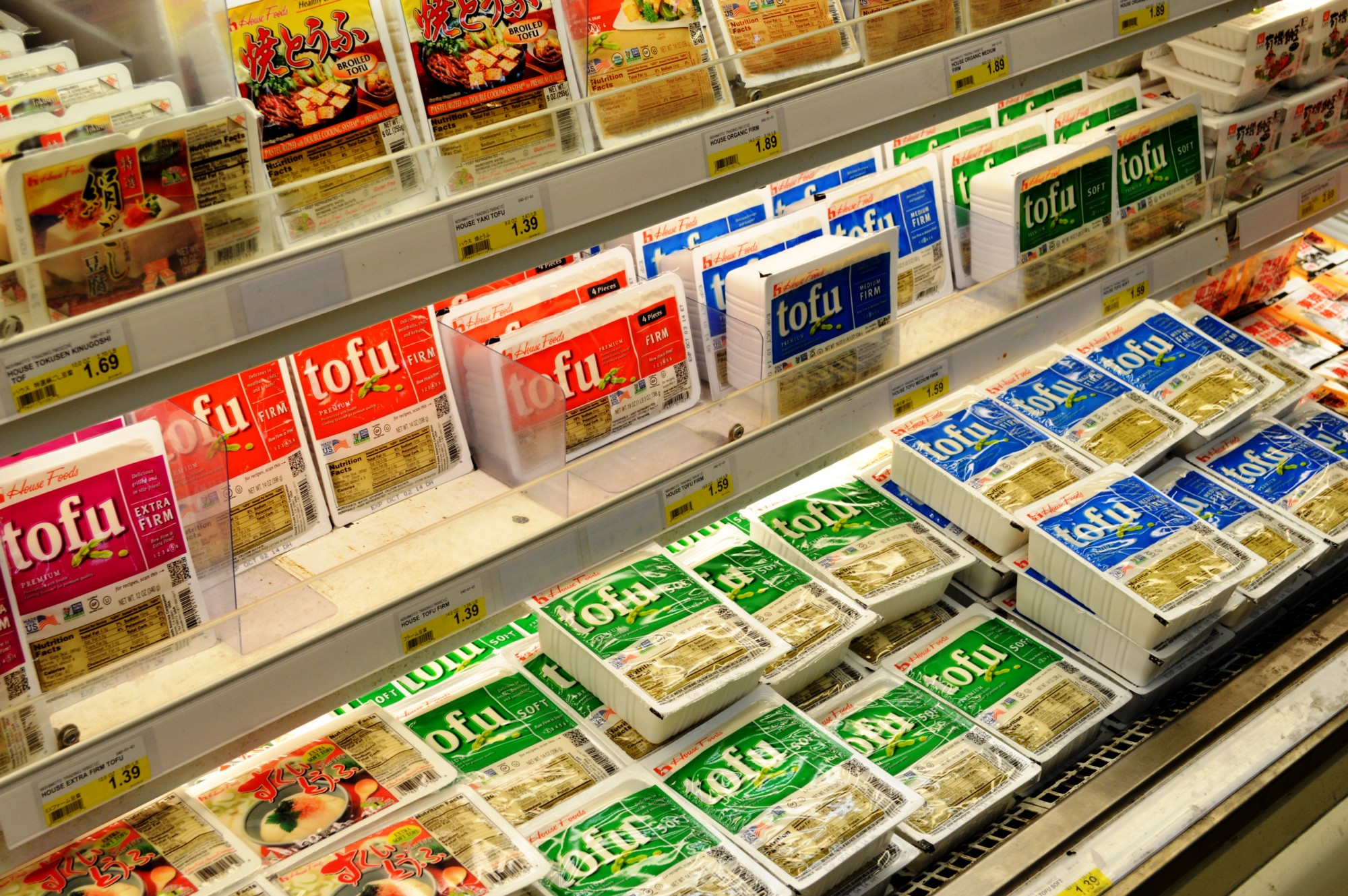 A grocery store refrigerated shelf stocked with many tubs of tofu — firm, extra-firm, and silken in different colors