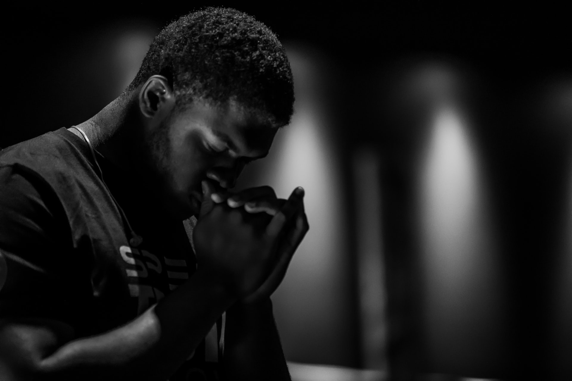 Man praying with his hands clasped together