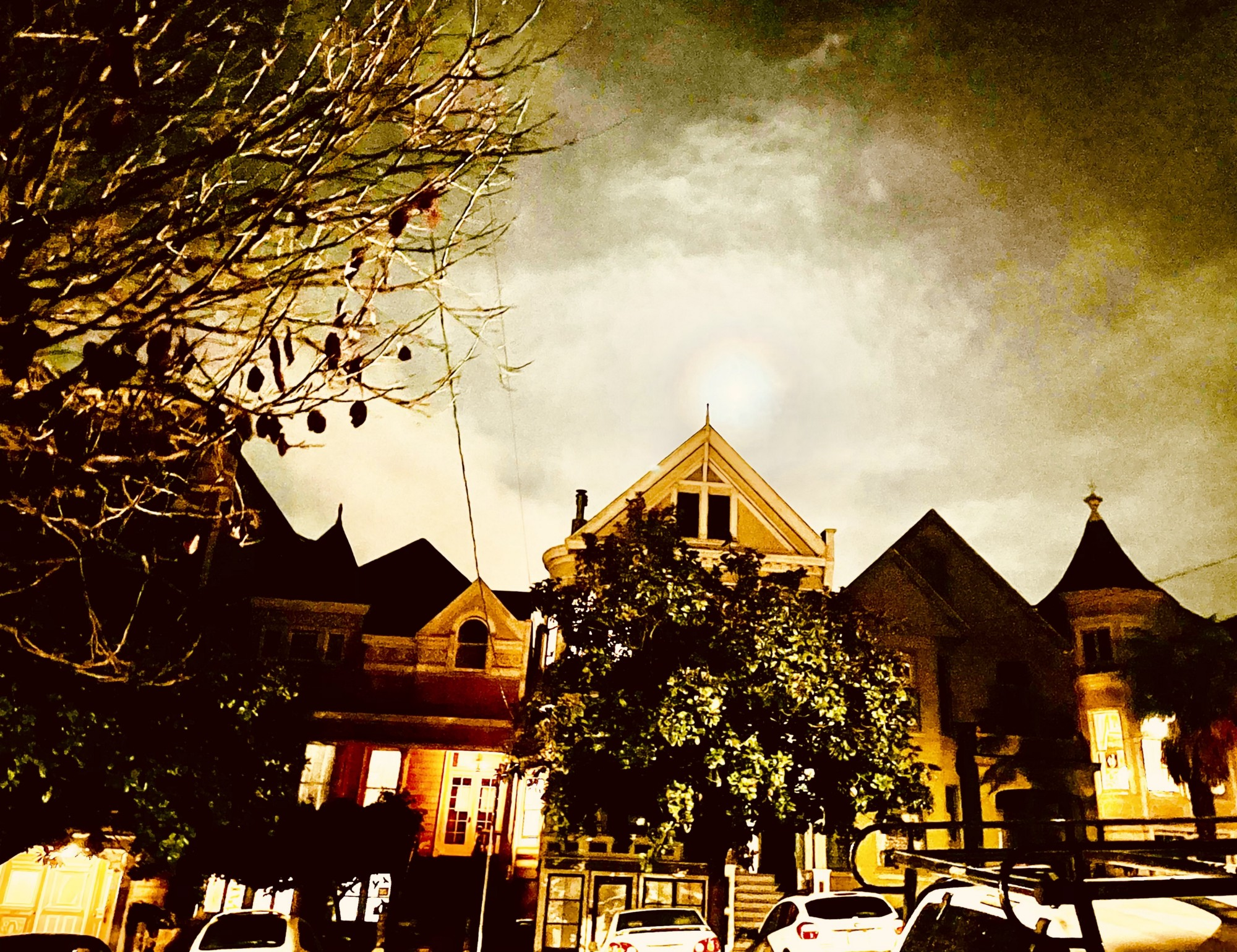 Four San Francisco Victorians act as sentinels by the light of a full moon surrounded by clouds full of foreboding.