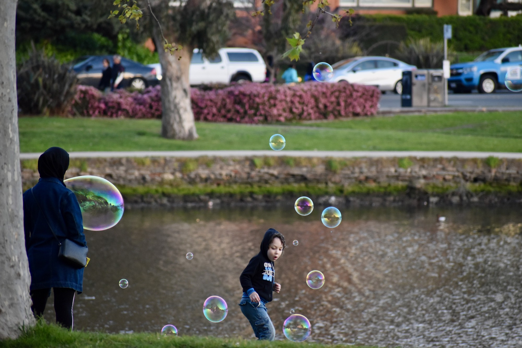 A child plays with large soap bubbles on a lake shore.